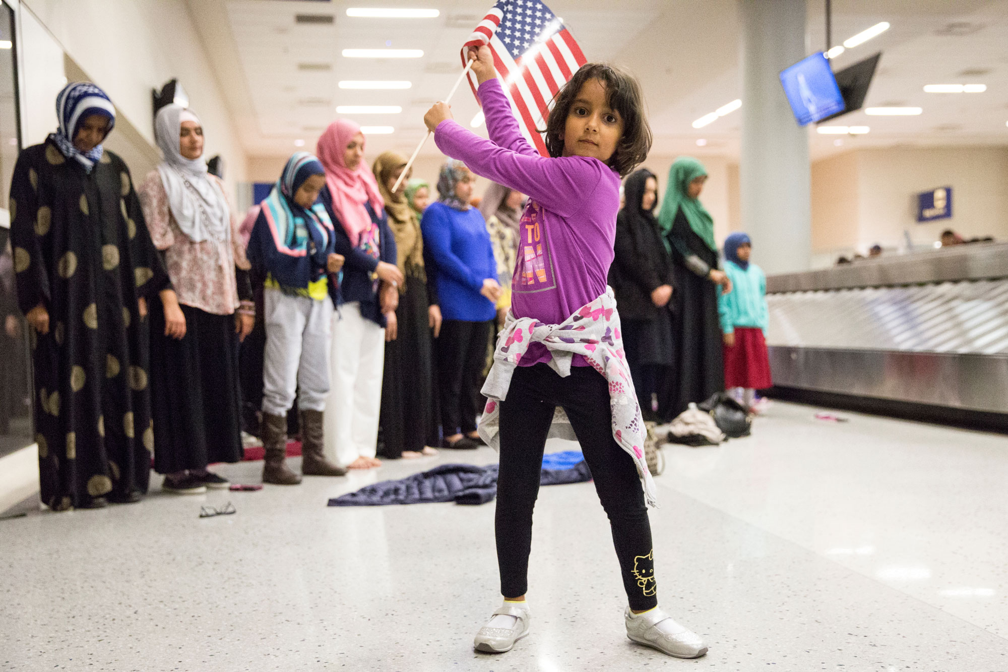 A young girl dances with an American flag in baggage claim while women pray behind her during a protest at the Dallas/Fort Worth International Airport.
