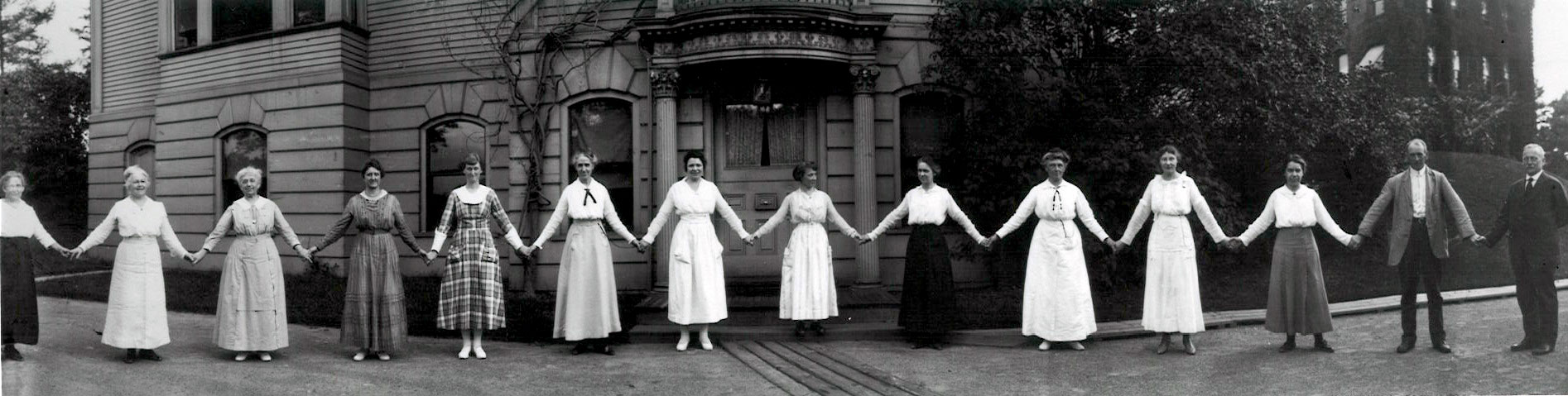 """A dozen women hold hands in front of a building on the Harvard campus in 1918. They are all women """"computers"""" working in the Harvard College Observatory. At the far right of the image is Edward Pickering, the head of the Observatory who hired them all."""