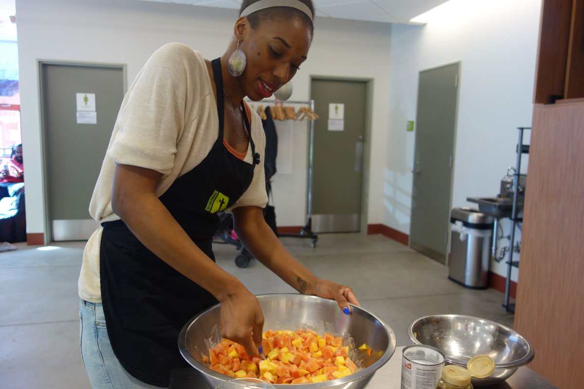 A student stirs up a mango and papaya fruit salad--a West African dessert with bits of coconut, peanuts and honey.