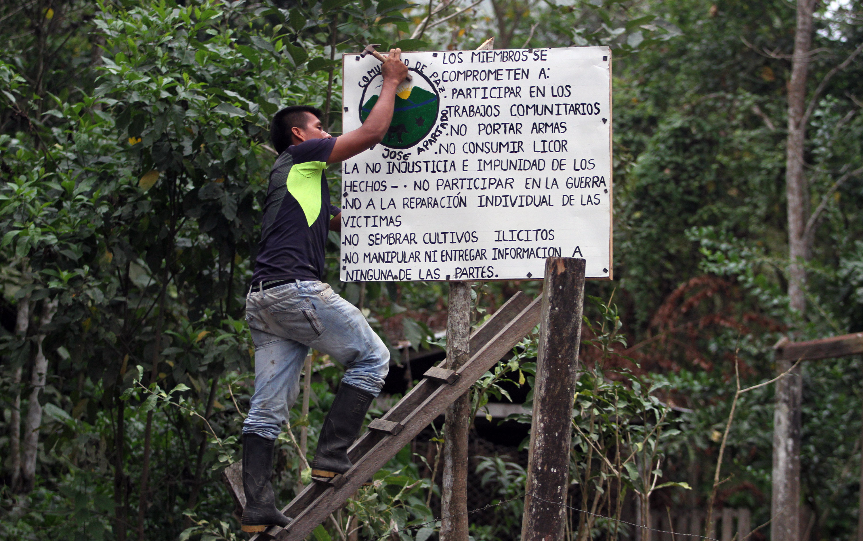 Germán, a community leader, hanging sign of community rules in preparation for 19th anniversary celebration