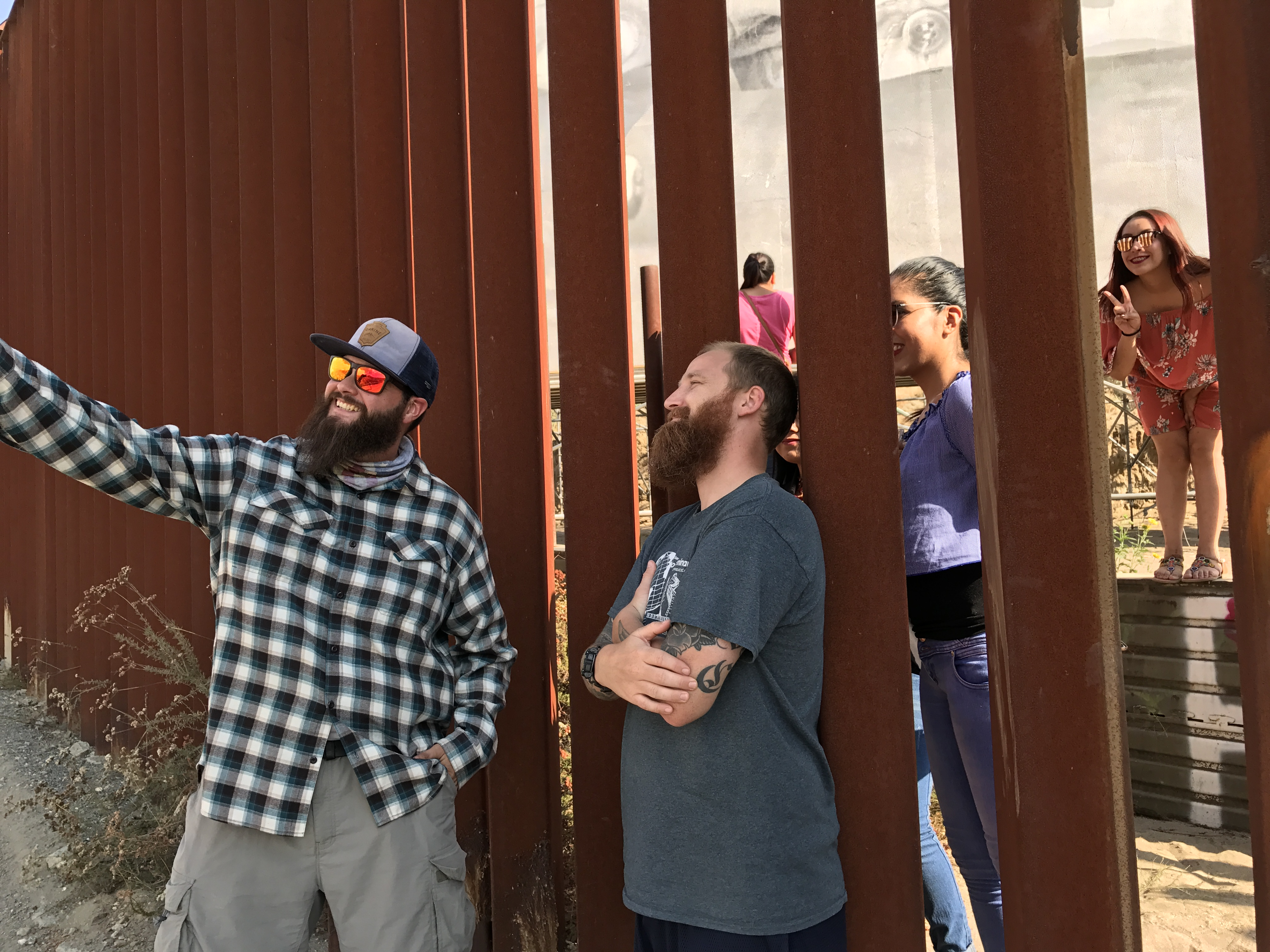 Two smiling men in beards hold up a phone as they stand in front of fence; on other side, you can see women smiling and making the peace sign with their fingers