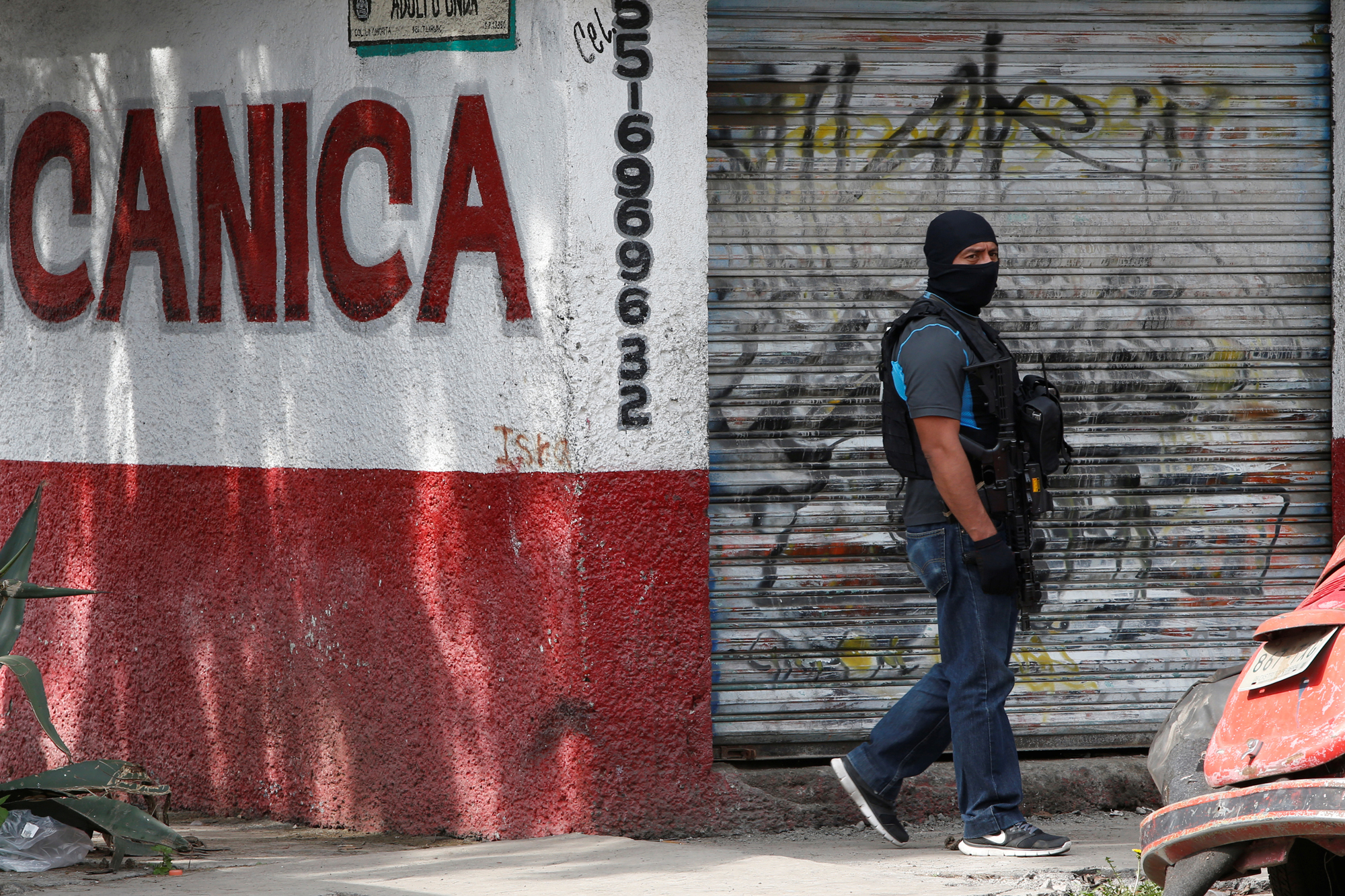 A Mexican police special agent guards an area after a shootout between gang members and the Mexican army in Mexico City.