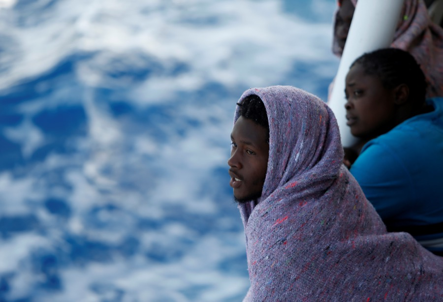 Migrants look out toward the Maltese island of Gozo, as the boat the Phoenix makes its way toward Italy after rescue operations off the coast of Libya, on May 5.
