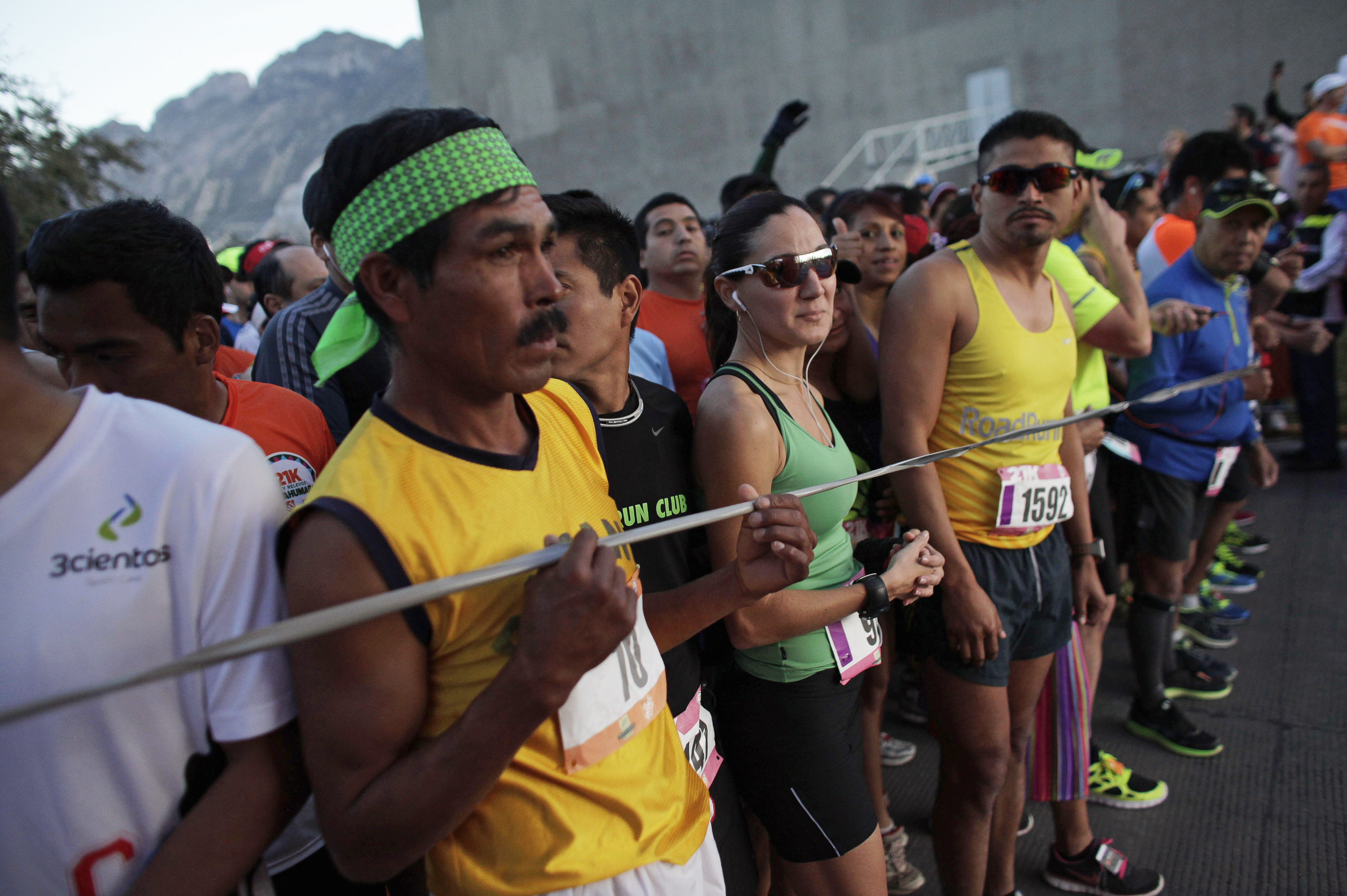 A Tarahumara man (front L) prepares next to other athletes before competing in a 21 km (13 miles) marathon in San Pedro Garza Garcia, on the outskirts of Monterrey, February 16, 2014.