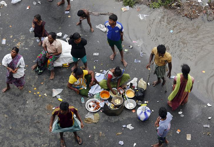 ​Displaced residents cook their meal on a flooded roadside in Chennai, India, December 3, 2015.