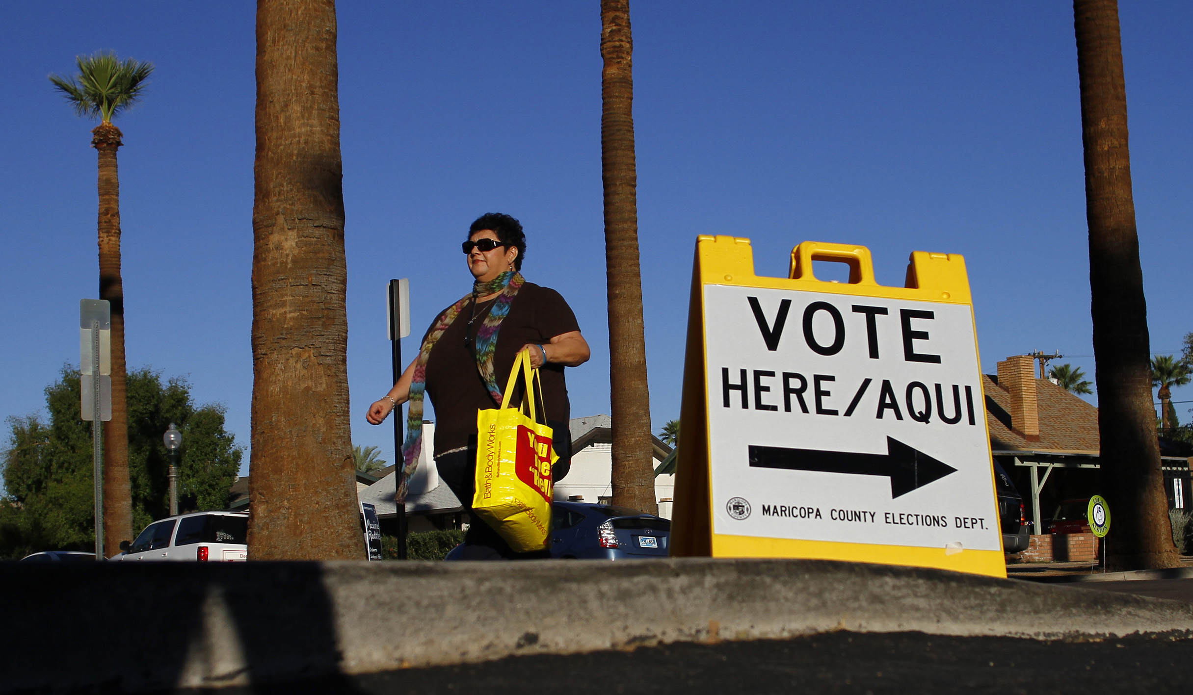 Woman walks past voter sign