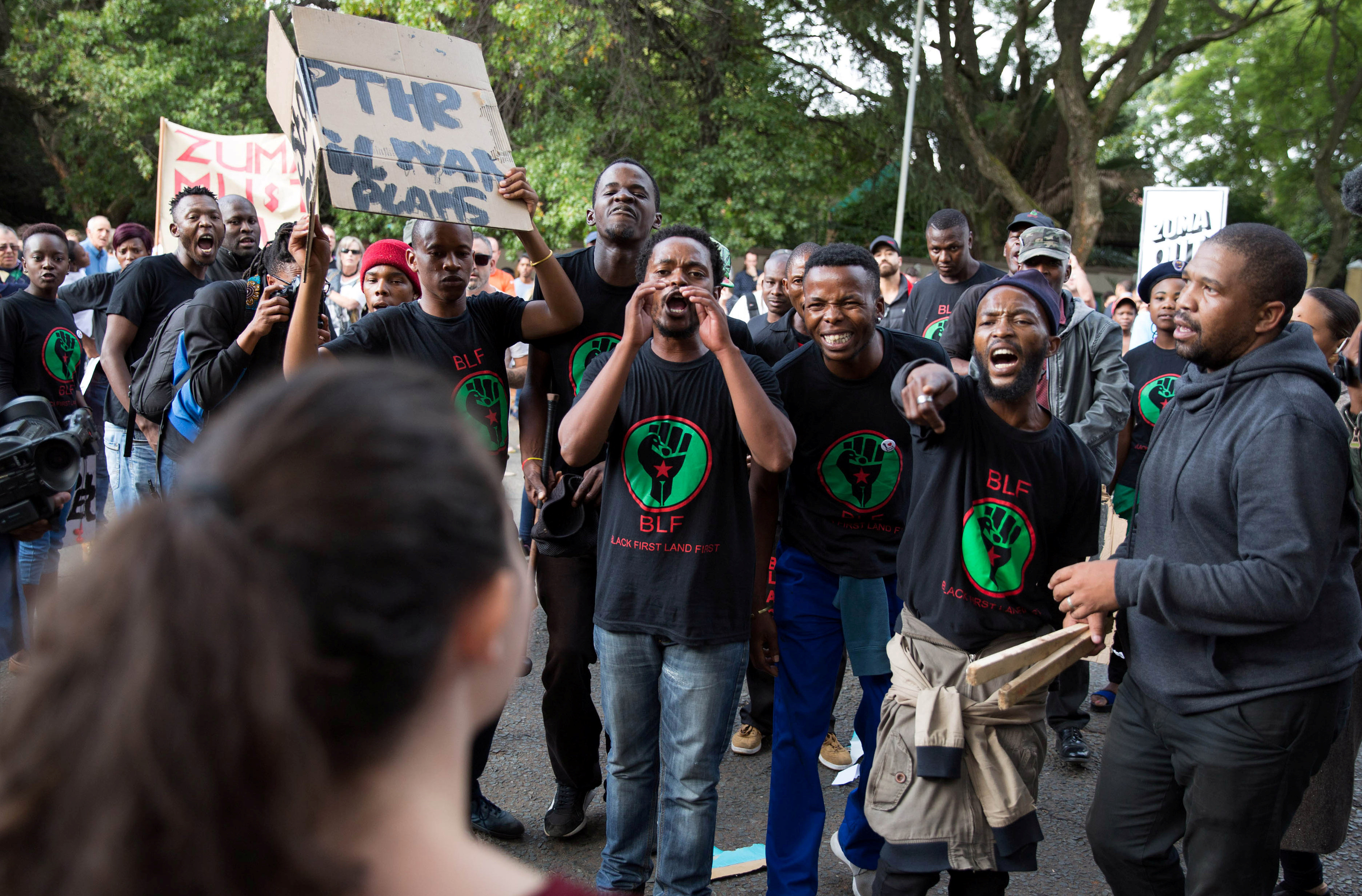 Supporters of President Jacob Zuma confront demonstrators calling for Zuma's removal outside the home of the controversial Gupta family in Johannesburg, South.
