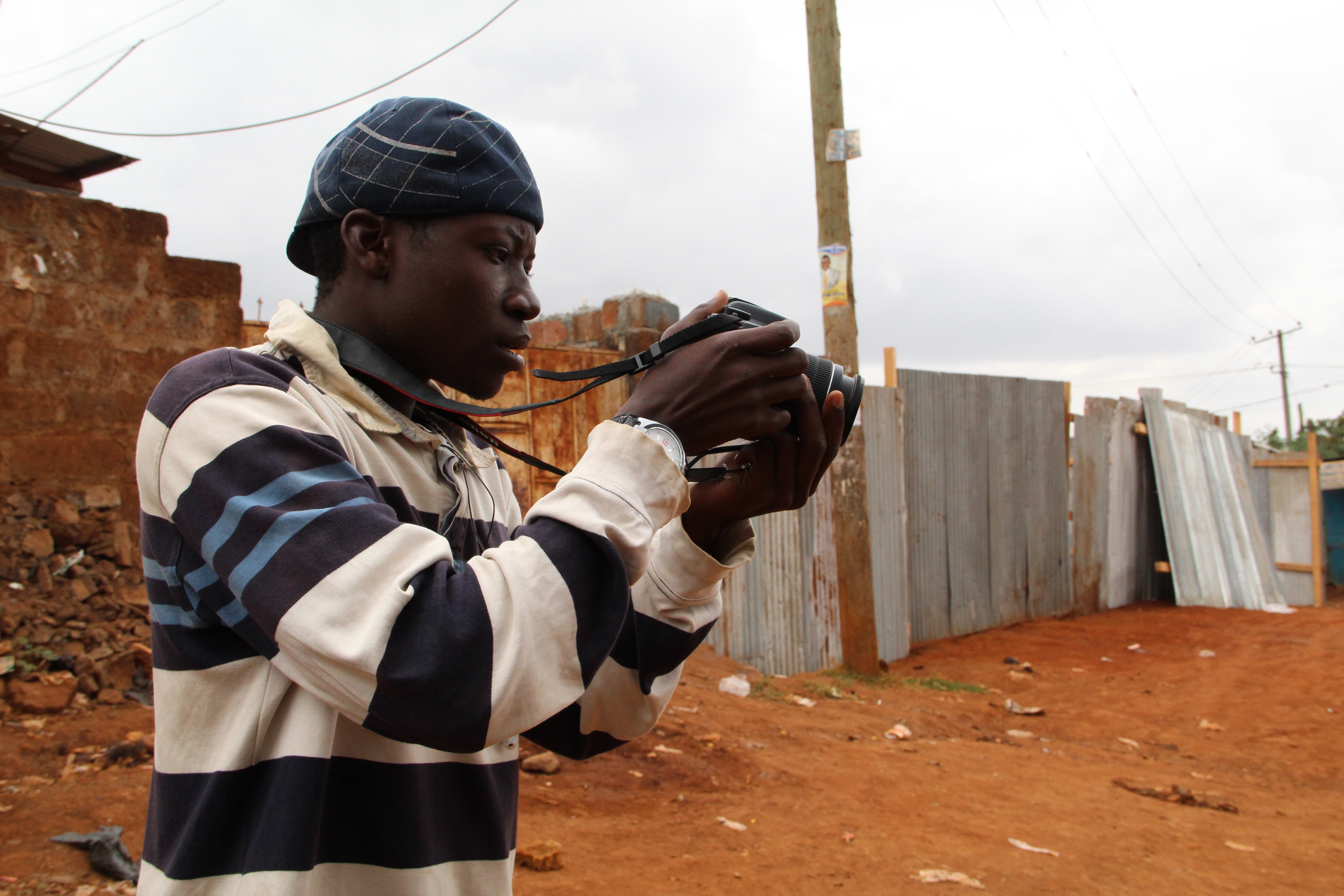 Abbas practices taking pictures with Habari Kibra's only camera. His true passion, though, is making radio.