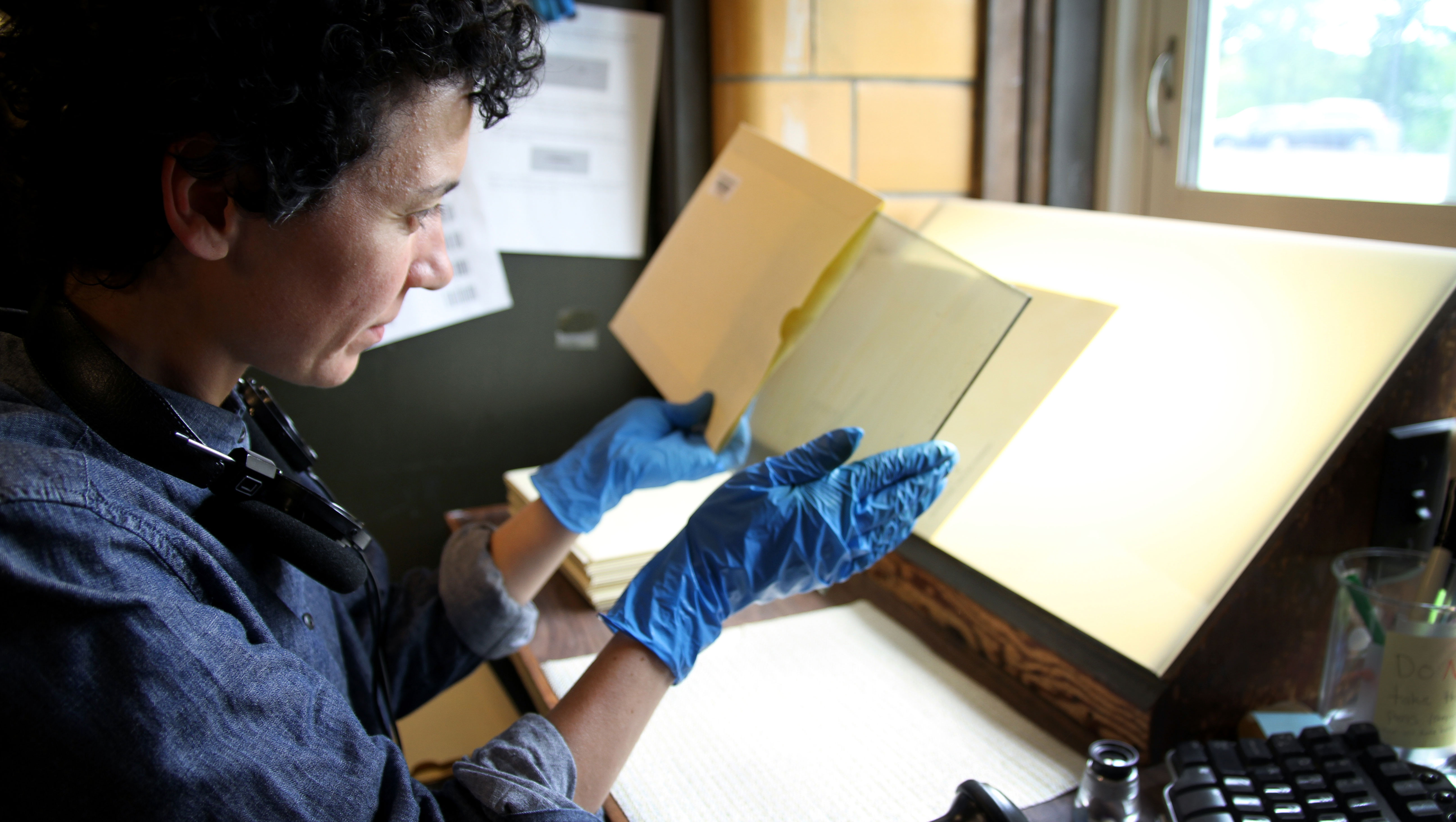 A woman holds up a glass plate, which she just removed from a paper envelope. She is staring at the plate, sitting in front of a window.