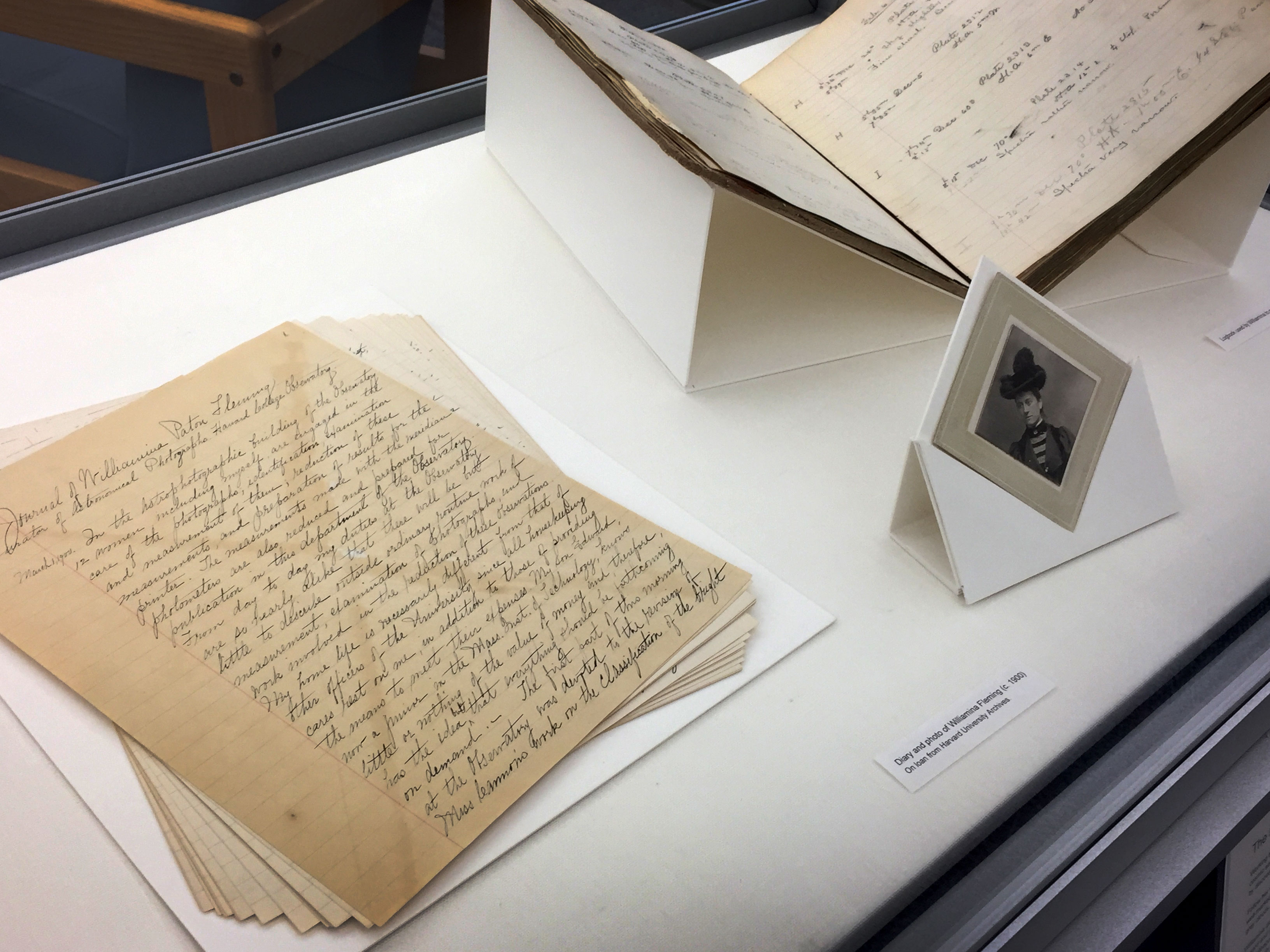 From left to right in a glass display case: yellowed pages with elegant handwritten script, a black and white portrait of Wilhelmina Fleming wearing a feathered hat; a yellowed logbook with mathematical notations in it.