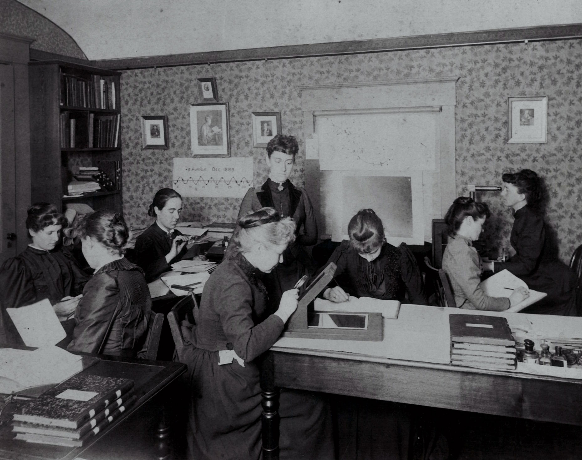 A group of women are sitting in a tiny room, some holding magnifying glasses, bent over boxes studying the glass plates. One stands in the center of the room, overseeing them. This is Williamina Fleming.