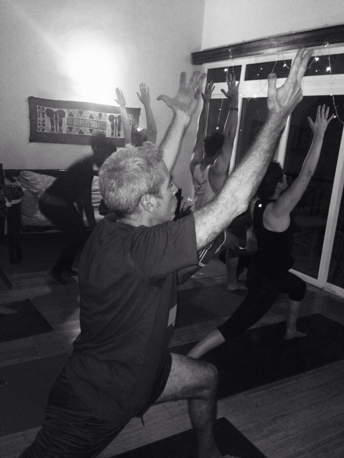 Marco Werman strikes the warrior 1 pose in Catherine Njeri's yoga class.