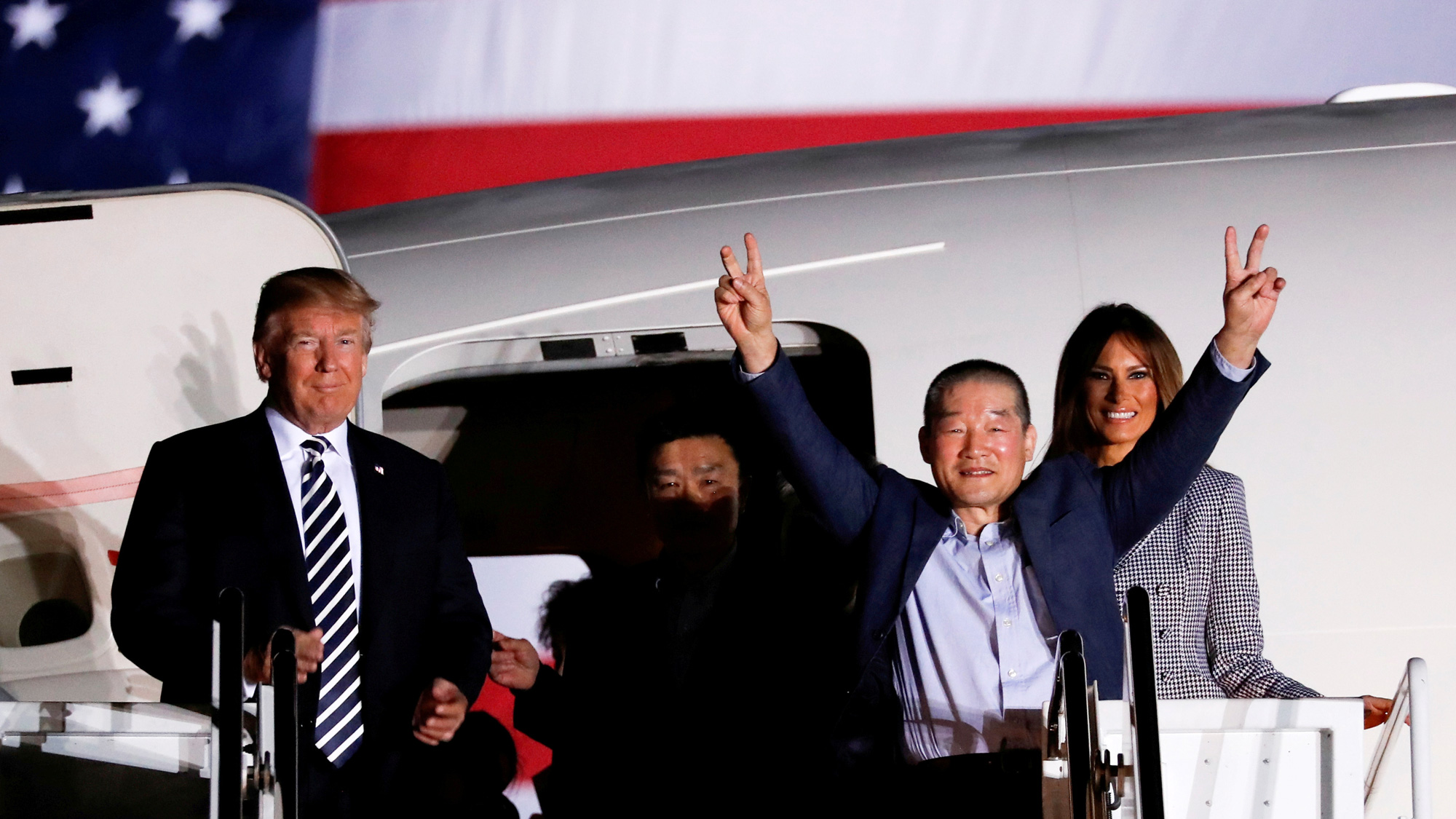 A man holds two fingers up on each hand as he exits an airplane. On the left is Donald Trump. Melania Trump is on the right.
