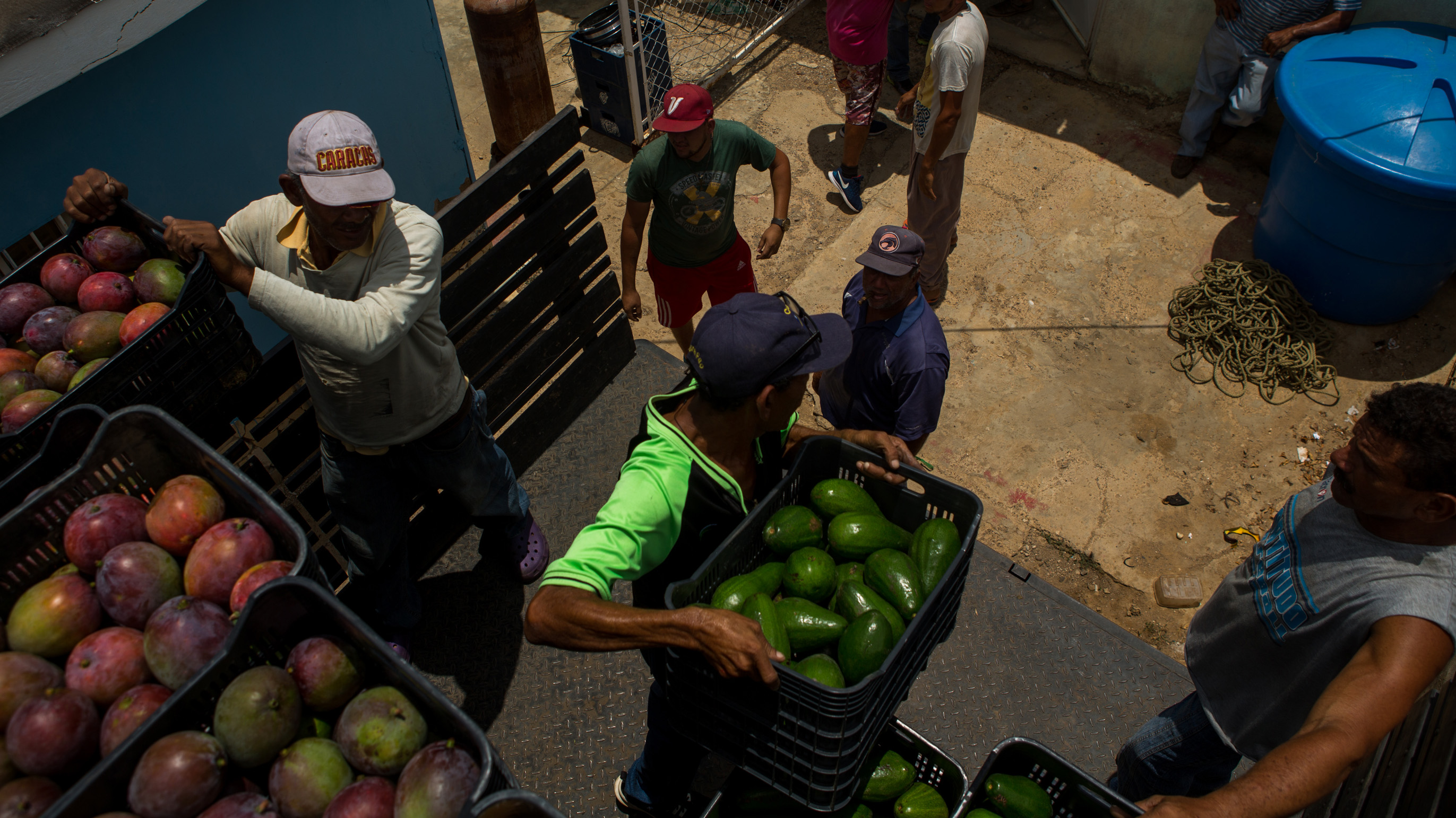 Workers unload produce for sale at a market in Caracas. It's increasingly hazardous work to drive a food delivery truck in Venezuela.