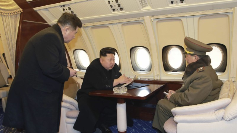 North Korean leader Kim Jong-un (C) talks with officials onboard his personal plane in this undated photo released by North Korea's Korean Central News Agency (KCNA) in Pyongyang Feb. 15, 2015.