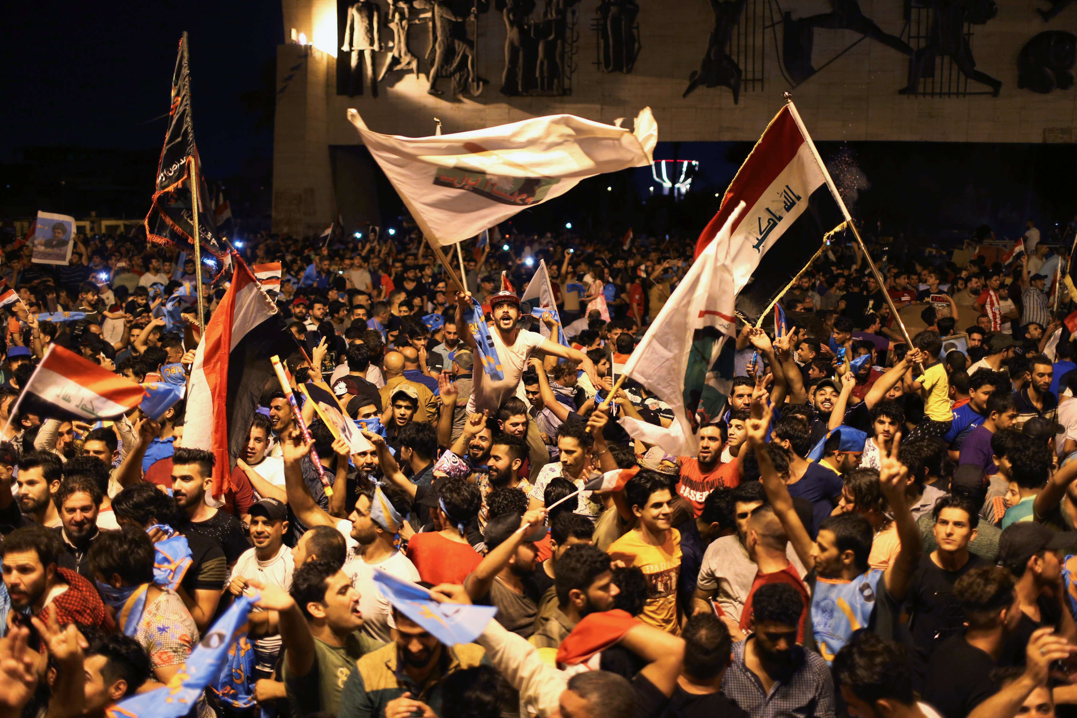 Iraqi supporters of cleric Moqtada al-Sadr's Sairun coalition celebrate after results of Iraq's parliamentary election were announced in Baghdad, Iraq, on May 14, 2018.
