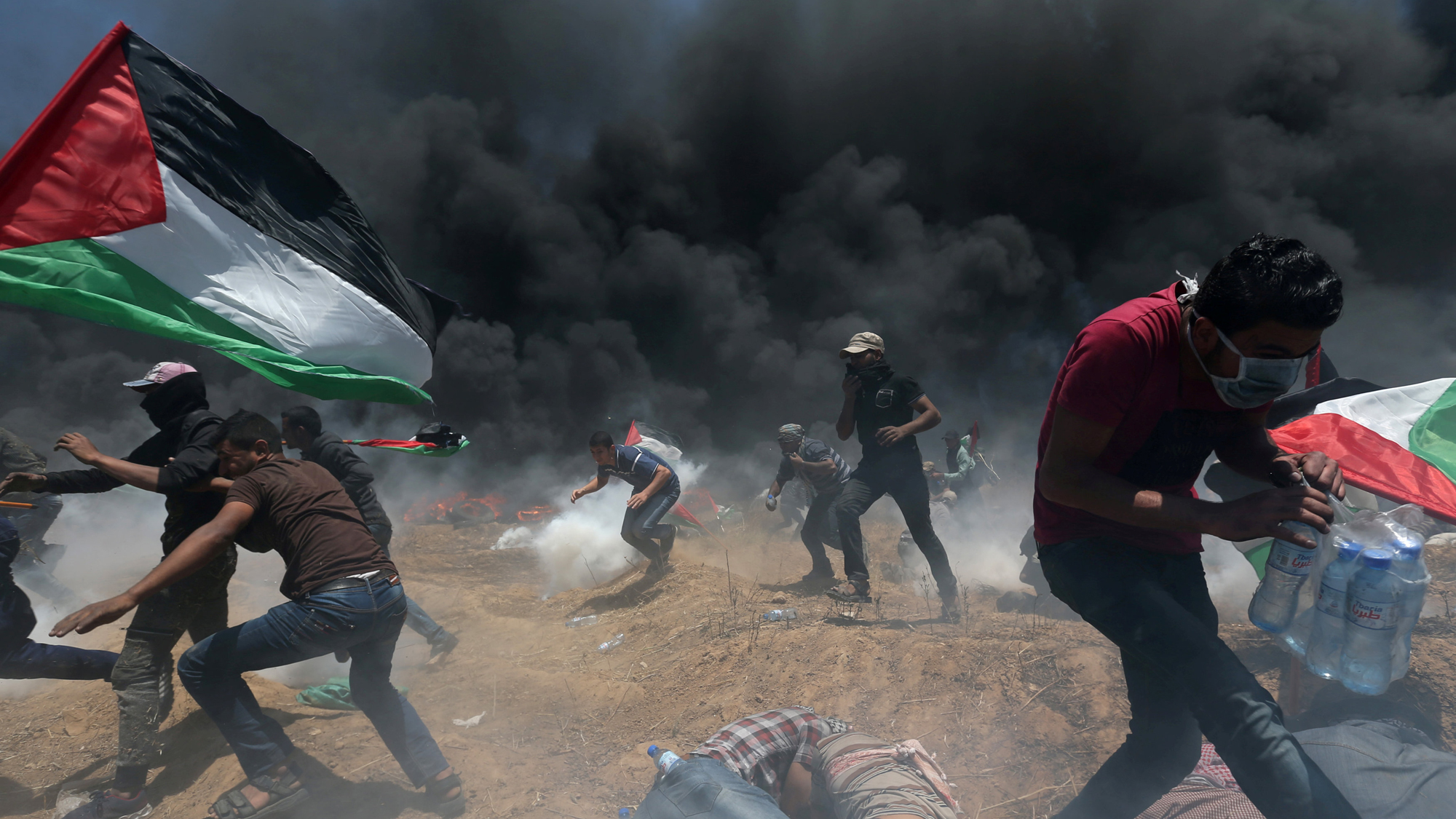 Palestinian demonstrators run for cover from Israeli fire and tear gas during a protest against US embassy move to Jerusalem, May 14, 2018.