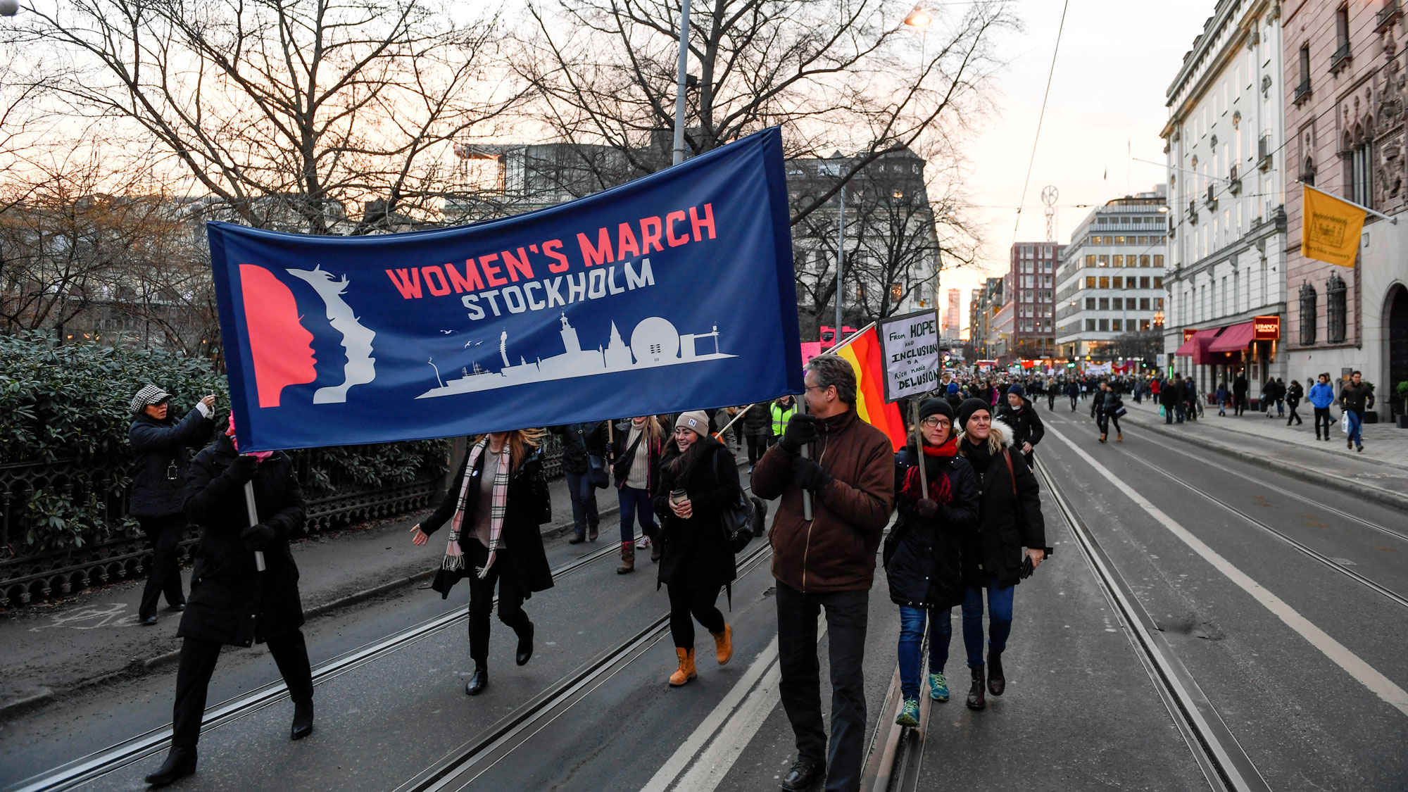 """People carry a large banner that says """"Women's March Stockholm"""" down a wide city street."""