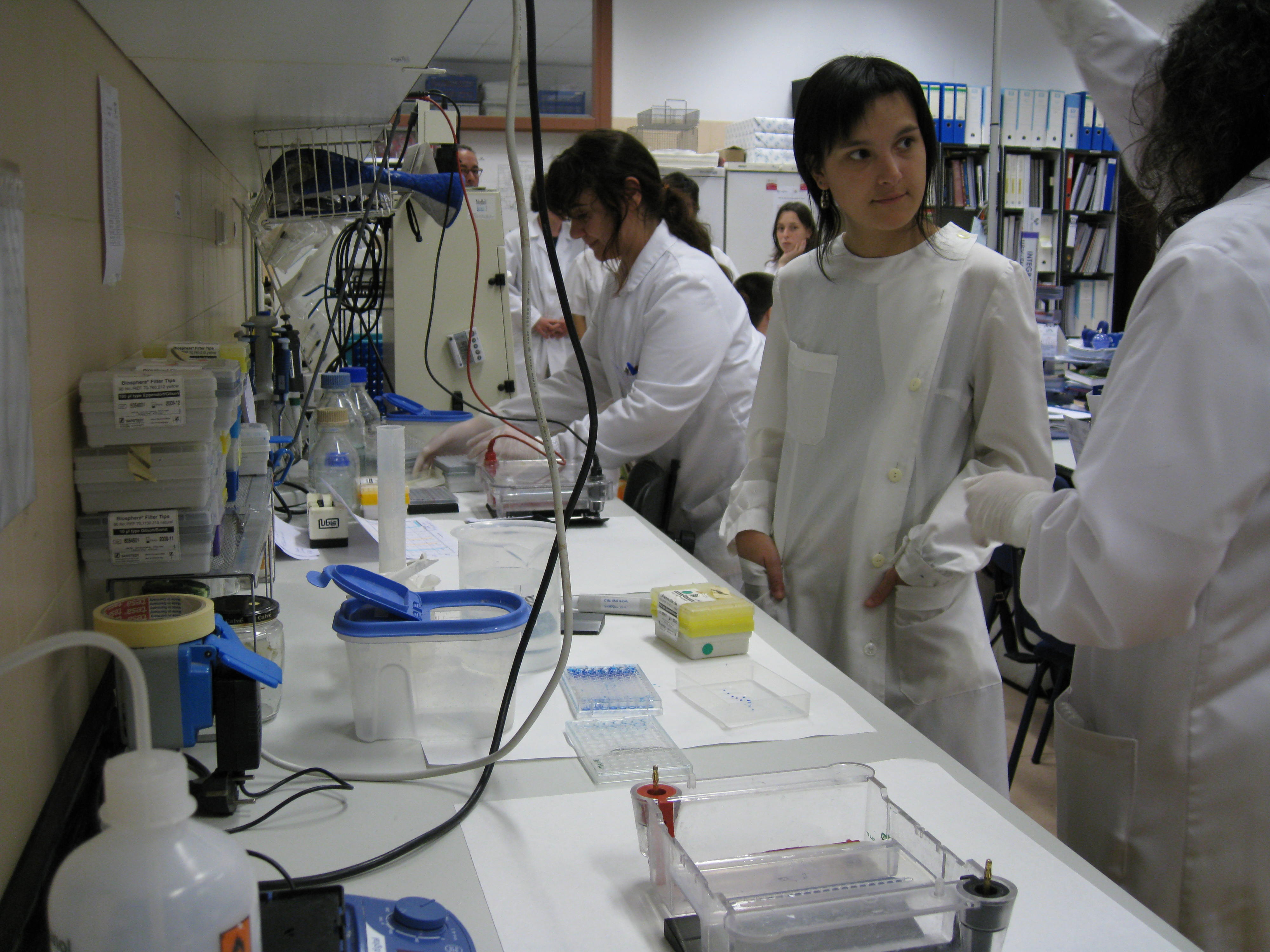 Workers in white suit at lab table with instruments