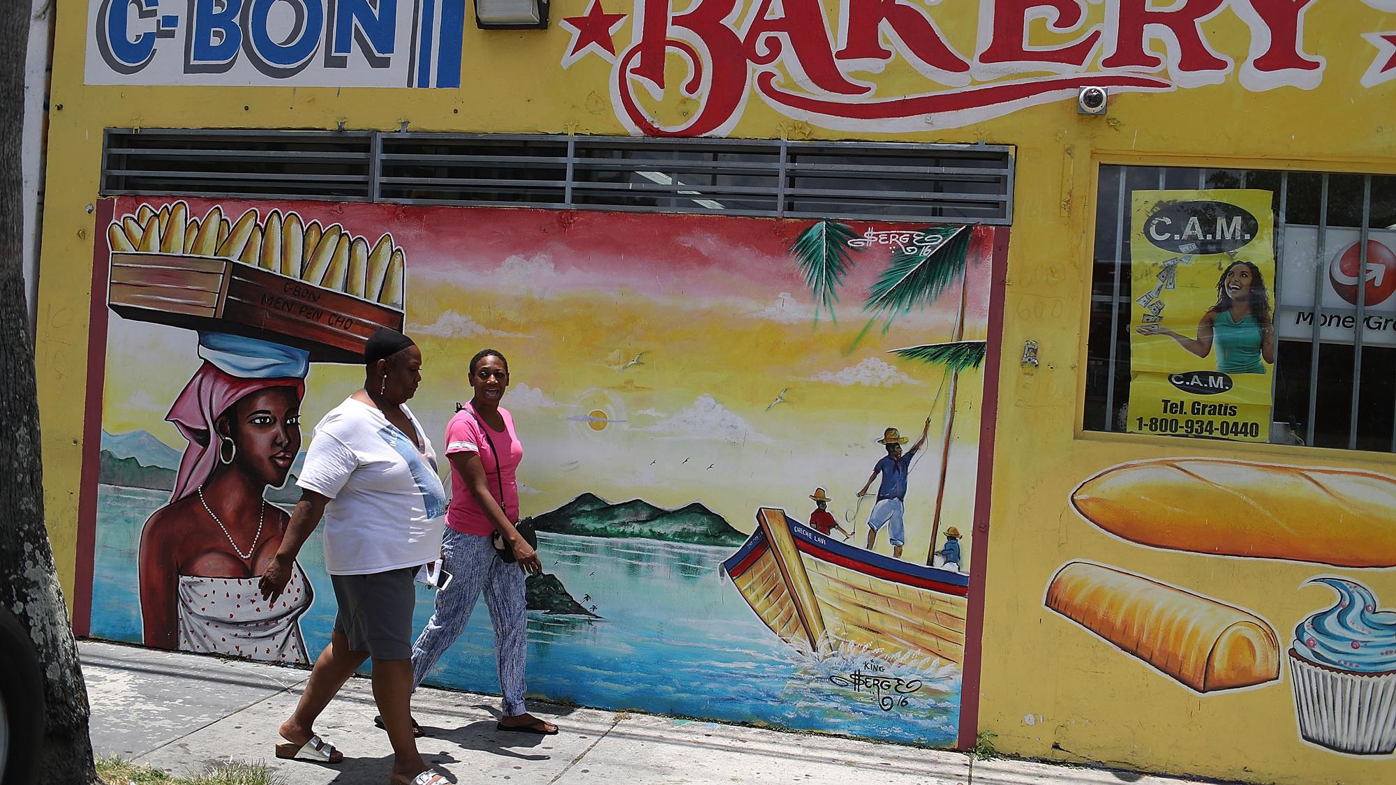 Women walk past a mural in the Little Haiti neighborhood in Miami, May 17, 2017.