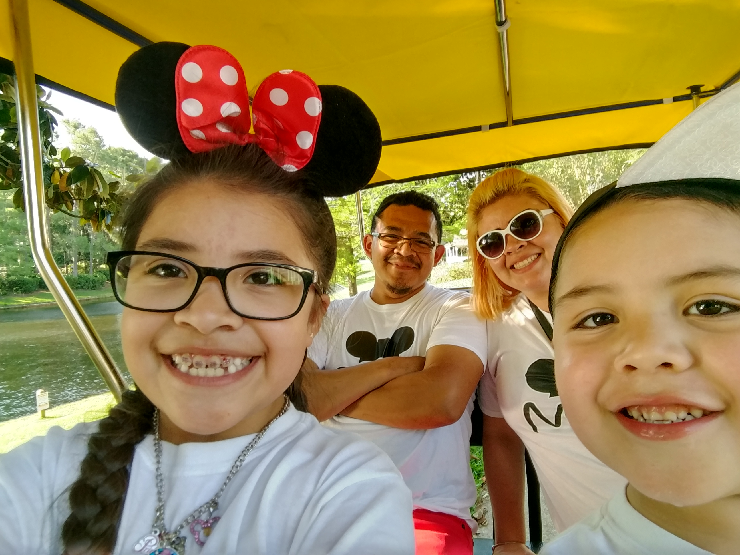 Family in cart, young girl in front with Mickey ears, young boy next to her, parents in back