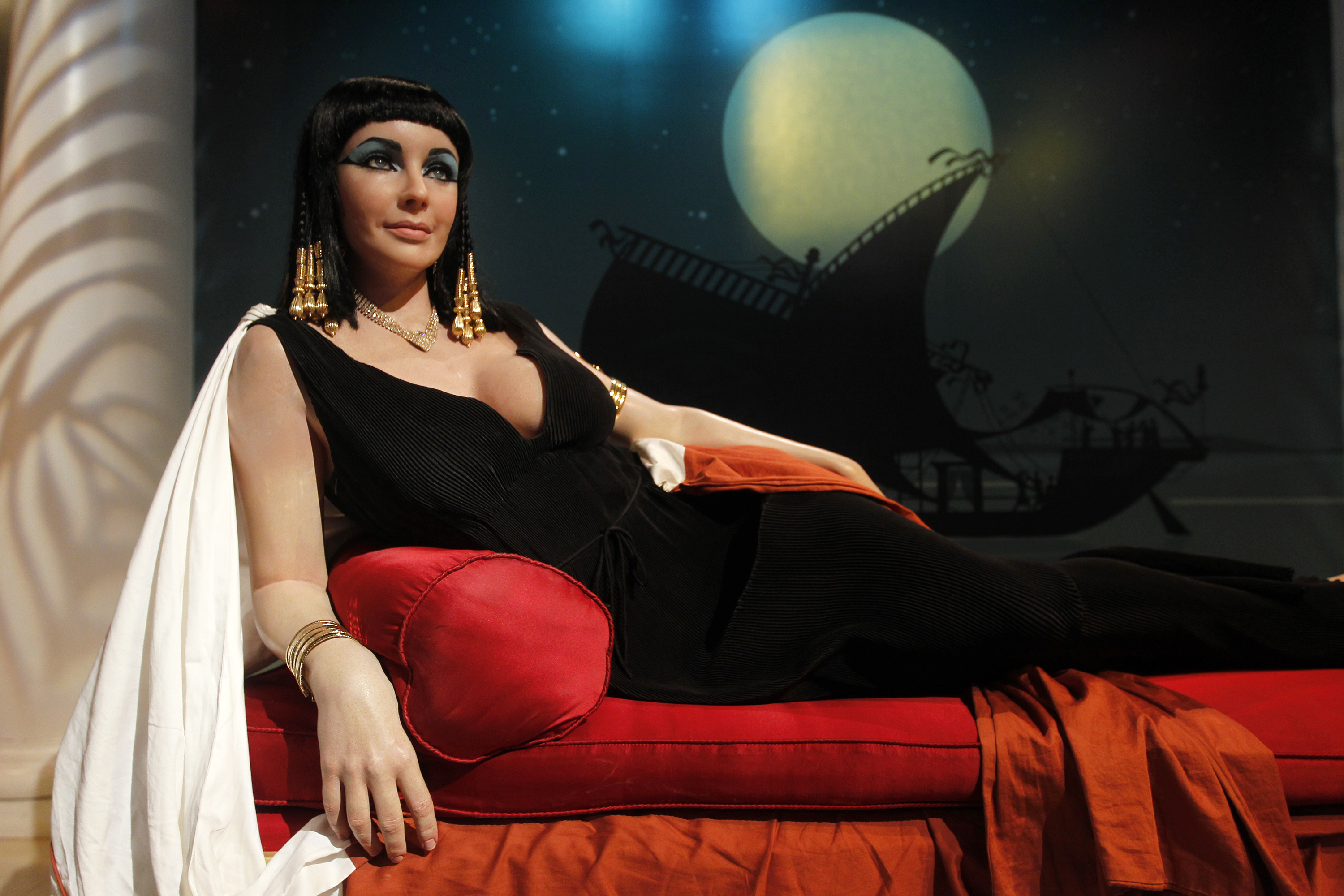 Elizabeth Tyler as Cleopatra lounges on a red cushion, he straight dark hair decorated with gold beads.