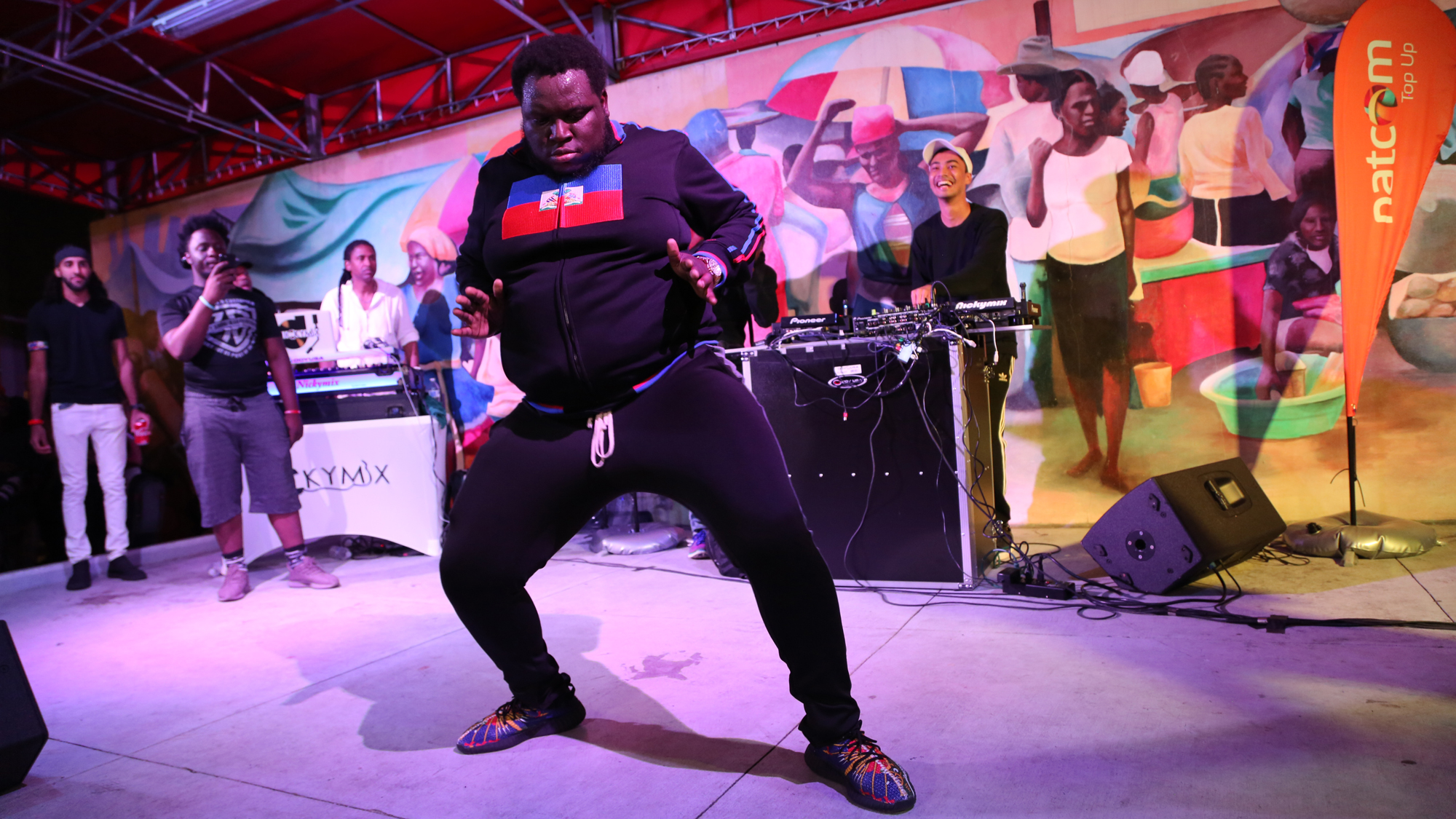 A fan dressed in a sweatshirt with the Haitian flag on it, joins DJ Michael Brun on stage at the Bayo Block Party in Miami, Flordia.