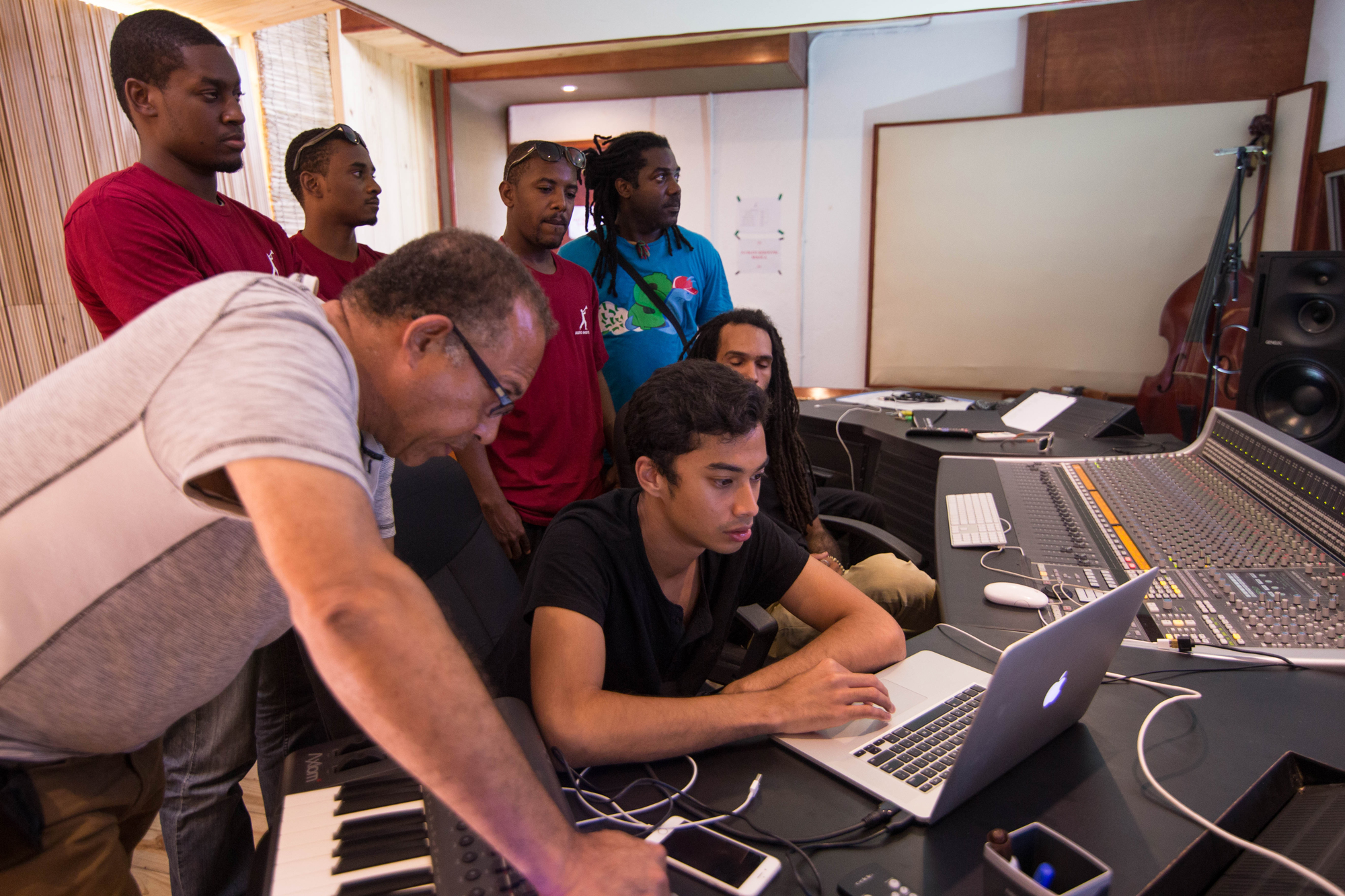 Michael Brun sits at a digital audio workstation with students at the Audio Institute in Jacmel, Haiti.