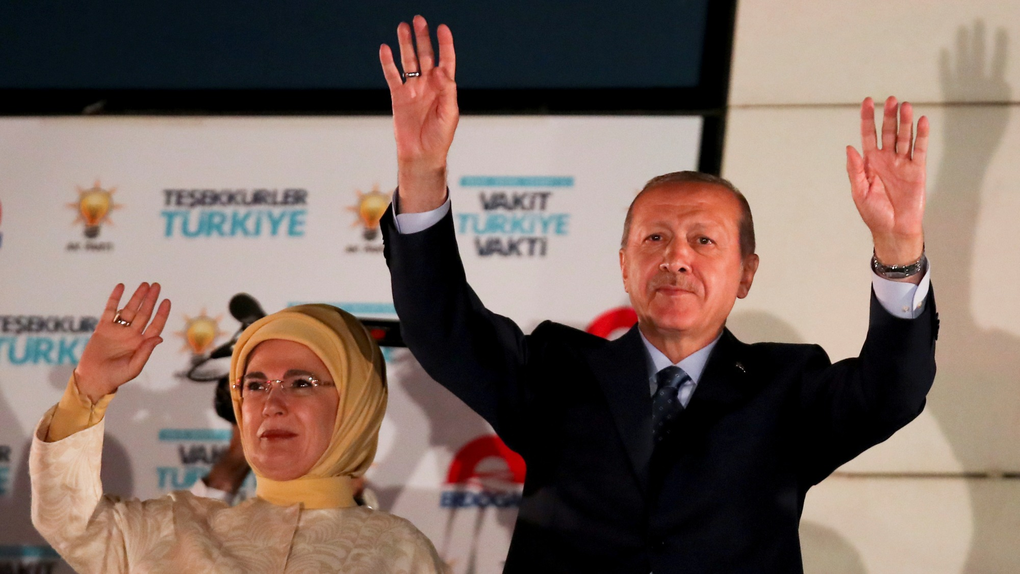 Turkish President Tayyip Erdoğan and his wife Emine Erdogan stand side-by-side with their arms up waving.