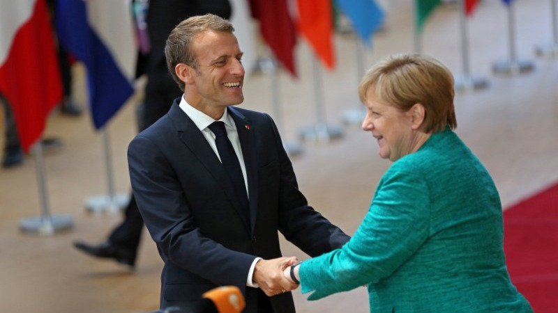 French President Emmanuel Macron, smiles as he warmly greets Germany's Chancellor Angela Merkel — the two holding hands.