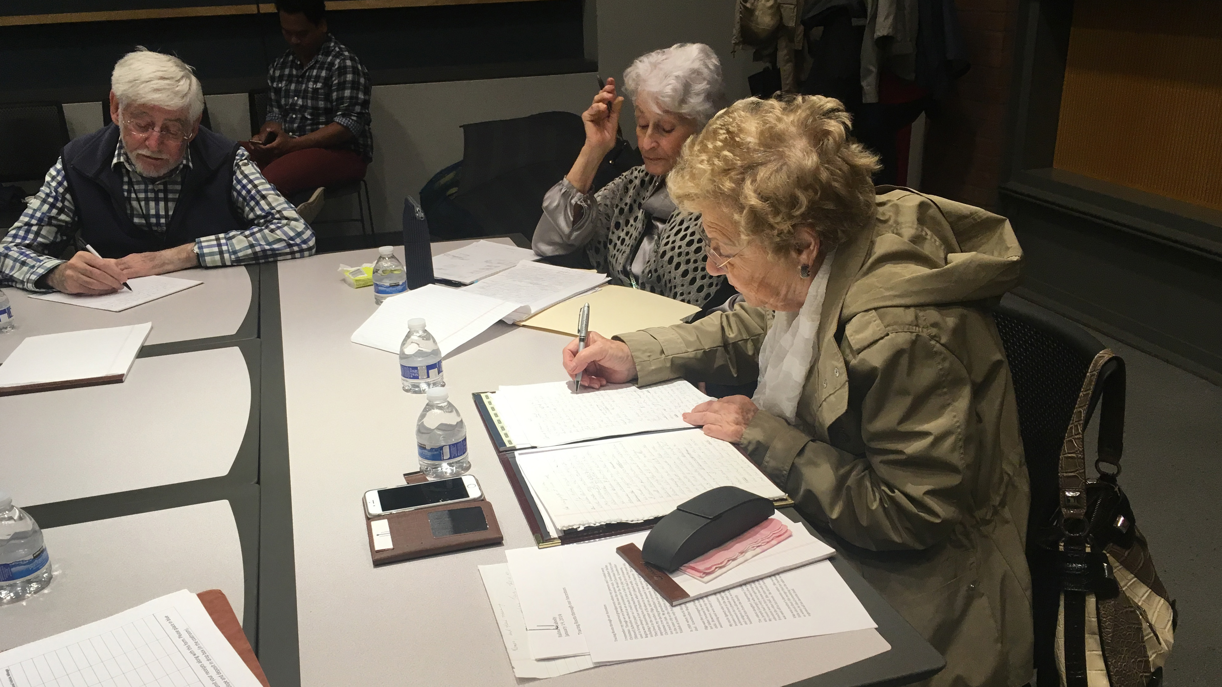 Three elderly Holocaust survivors sit at a table writing.