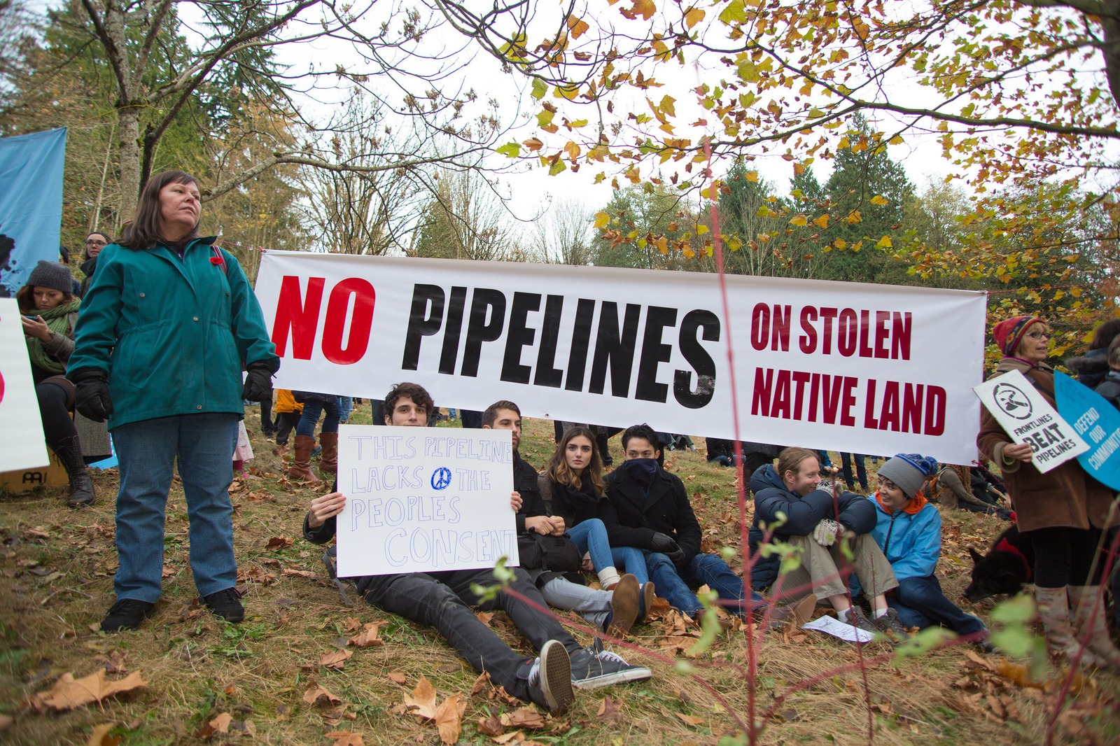 Protestors hold up signs at a rally against a proposed Kinder Morgan oil pipeline expansion on Burnaby Mountain in 2014 in British Columbia. In late May, the Canadian government announced it would fund an expansion project for the Kinder Morgan Trans Moun