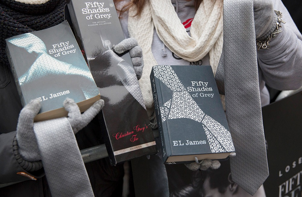"Fans pose with ""Fifty Shades of Grey"" paraphernalia at the film's UK premiere in London in 2015."