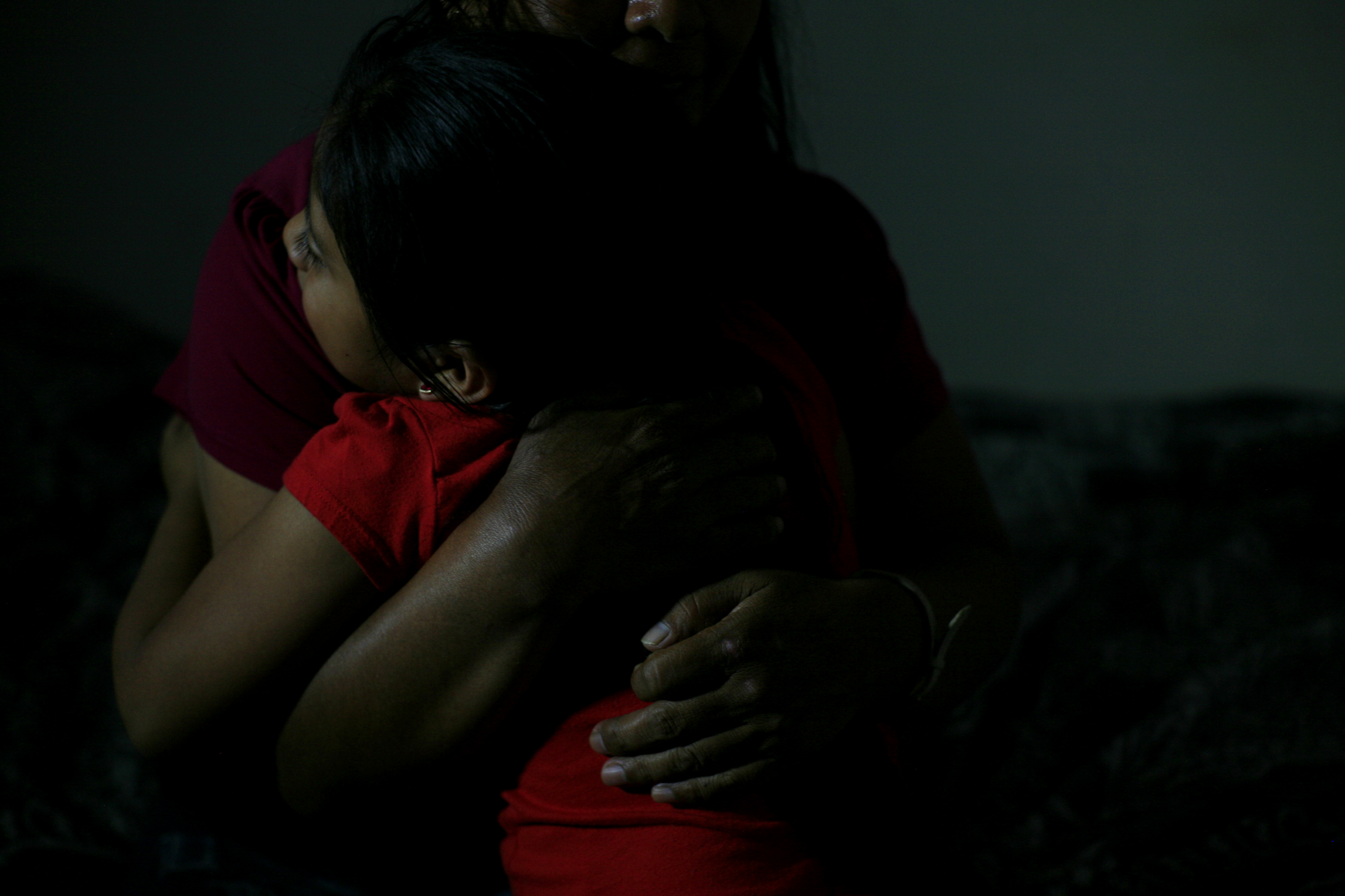 Woman embracing young girl, faces not shown