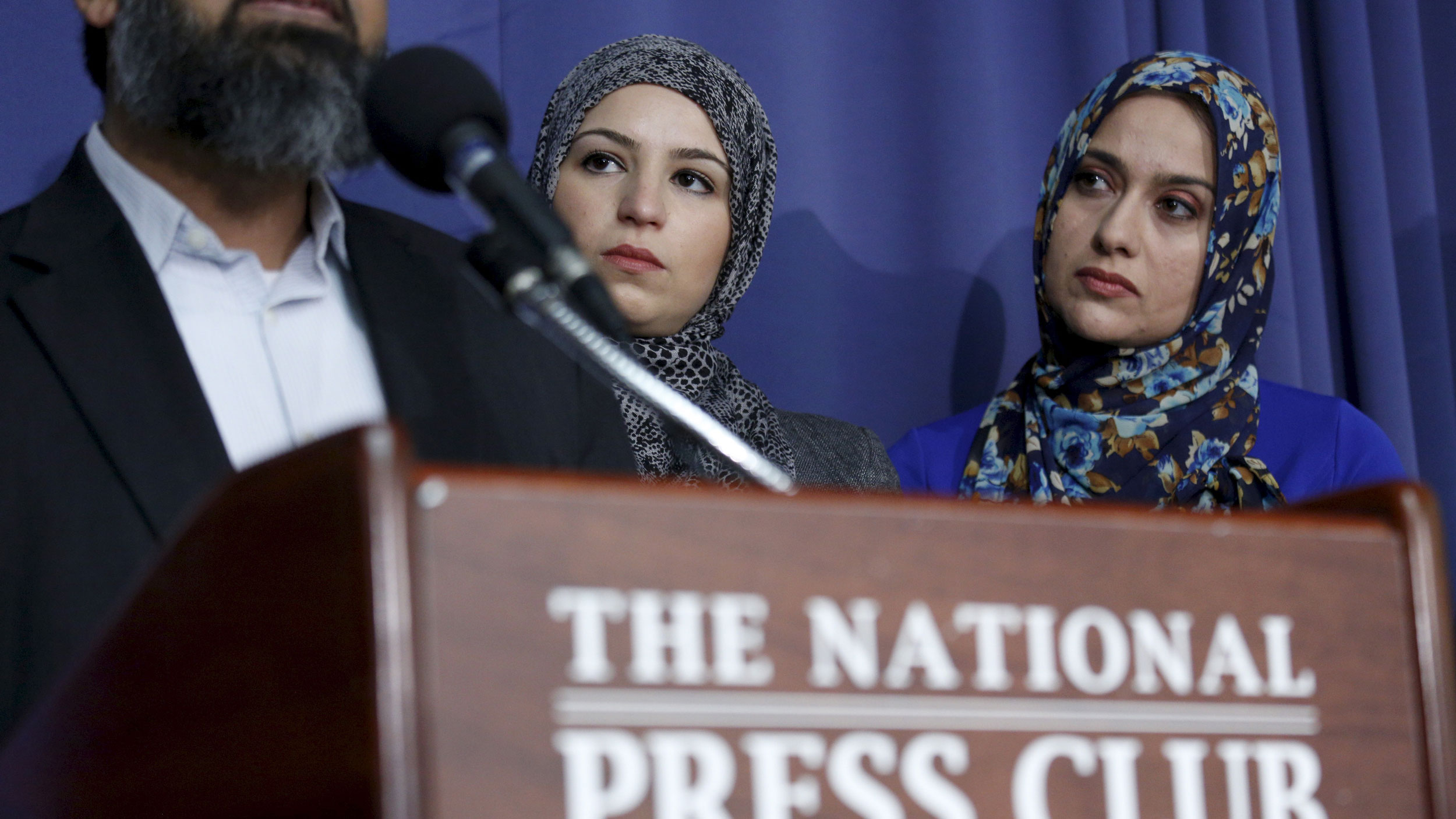 Two women wearing head scarves watch a man at a podium.