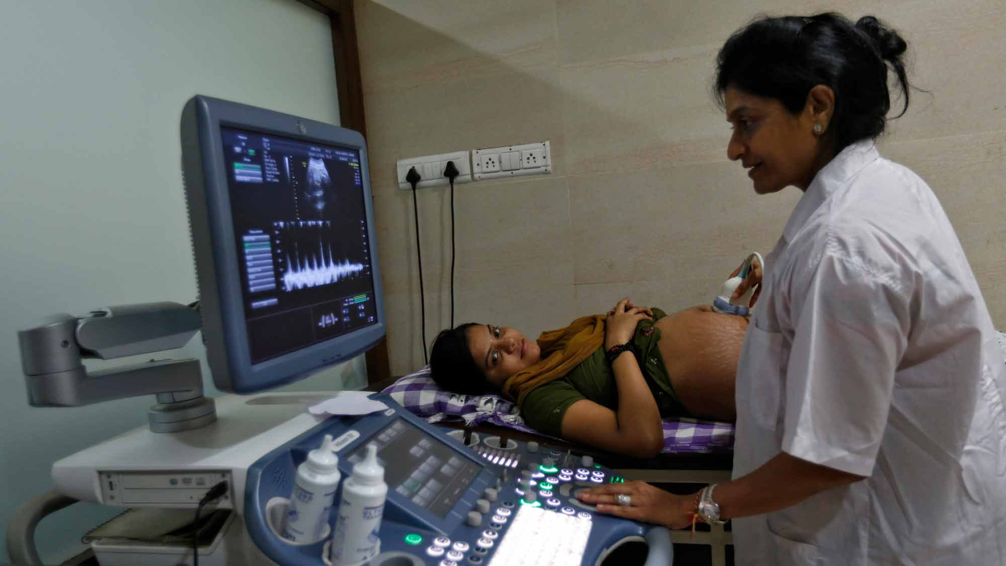 A female doctor performs an ultrasound on a pregnant patient.
