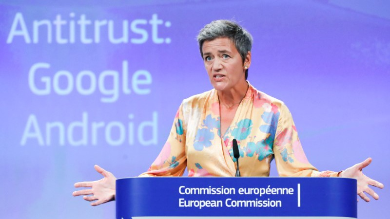 """European Competition Commissioner Margrethe Vestager stands at a podium with a screen behind her reading """"Antitrust: Google Android."""""""