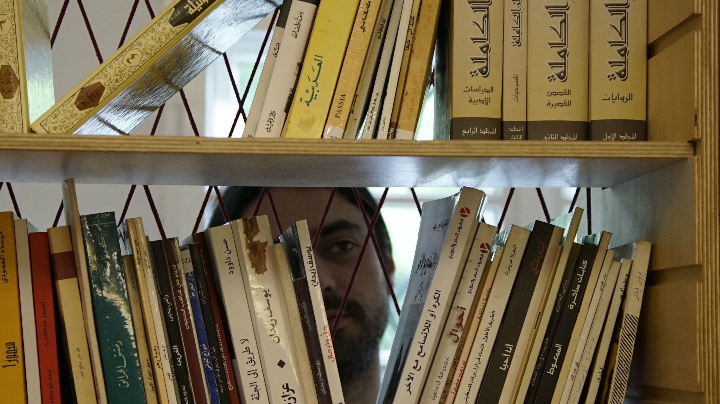 "Muhanned Qaiconie, a co-founder of Berlin's first Arabic-language public library, looks at books in the collection. ""All kinds of people come here,"" he said. ""We have older generations of Arabic speakers, new readers, seasoned bookworms, aspiring writers"