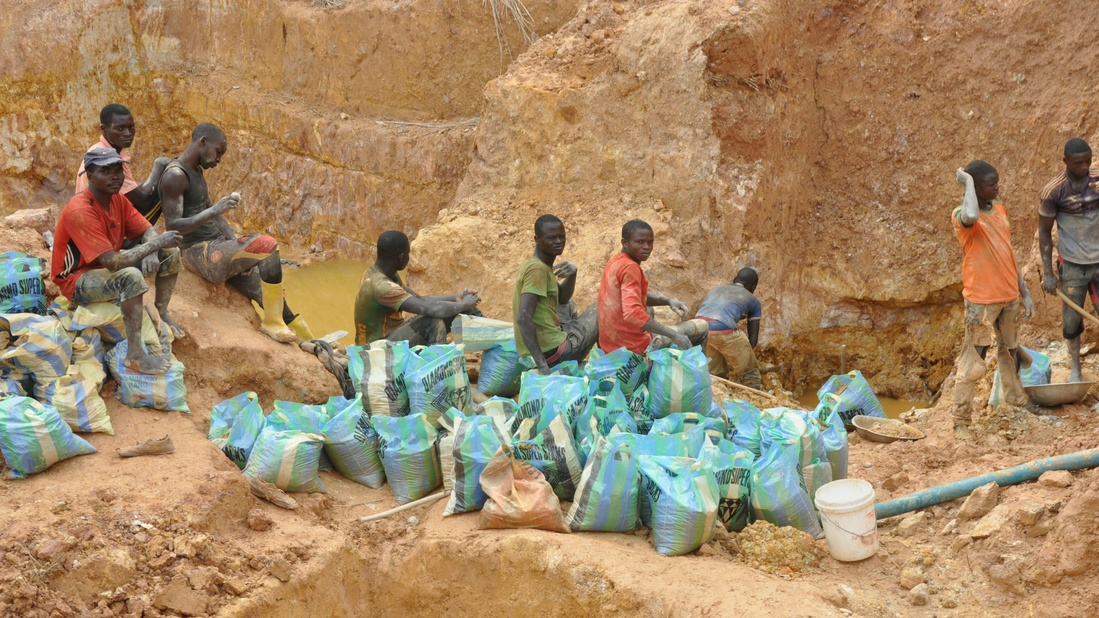 Local miners fill bags with gravel extracted from holes dug by Chinese mining machines in Ngoe Ngoe, Cameroon, Feb. 15, 2018.