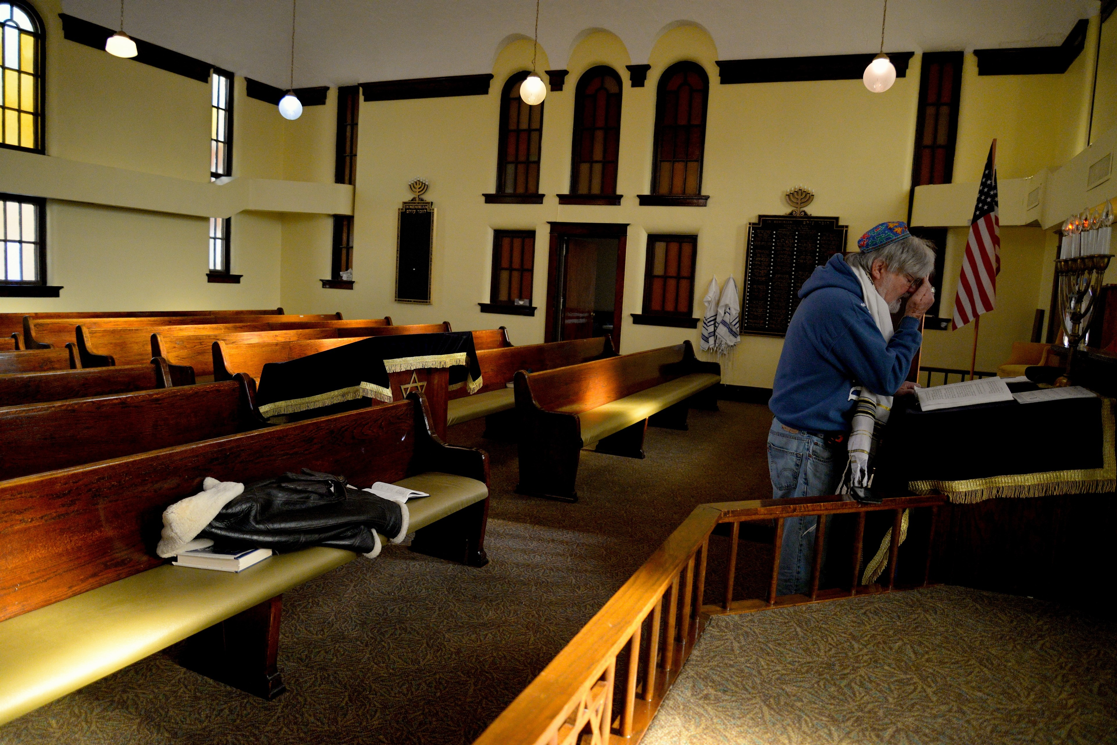 Jewish man prays at altar with pews behind him, USA flag in background
