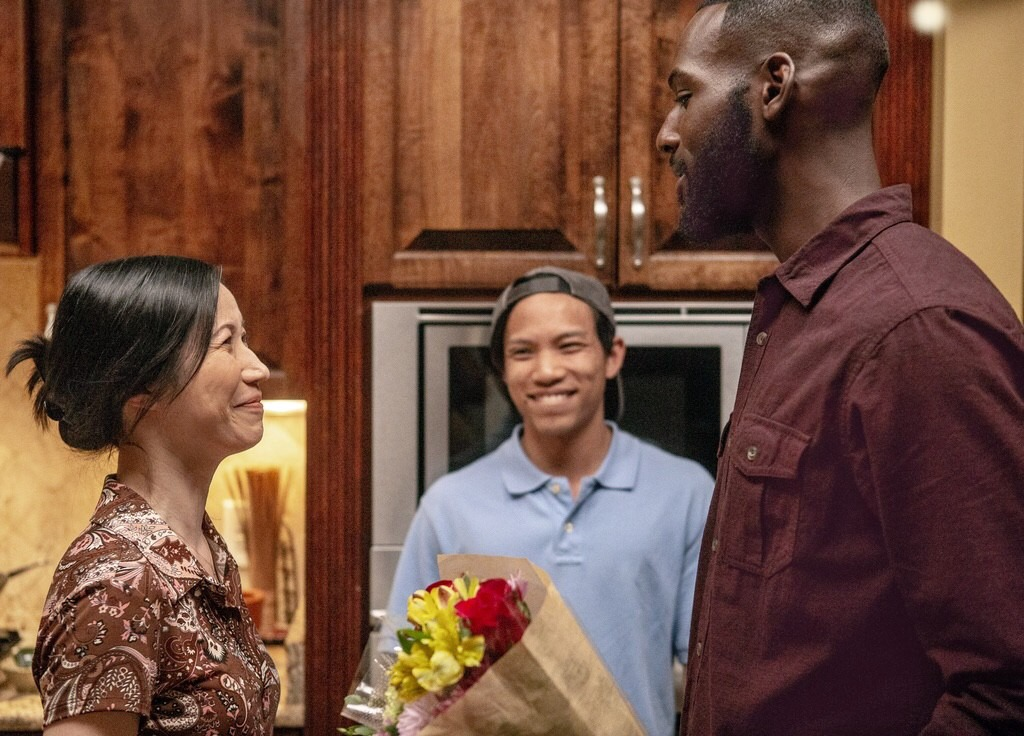 In front of wodden kitchen cupboards, older Vietnamese woman speaks to young black man