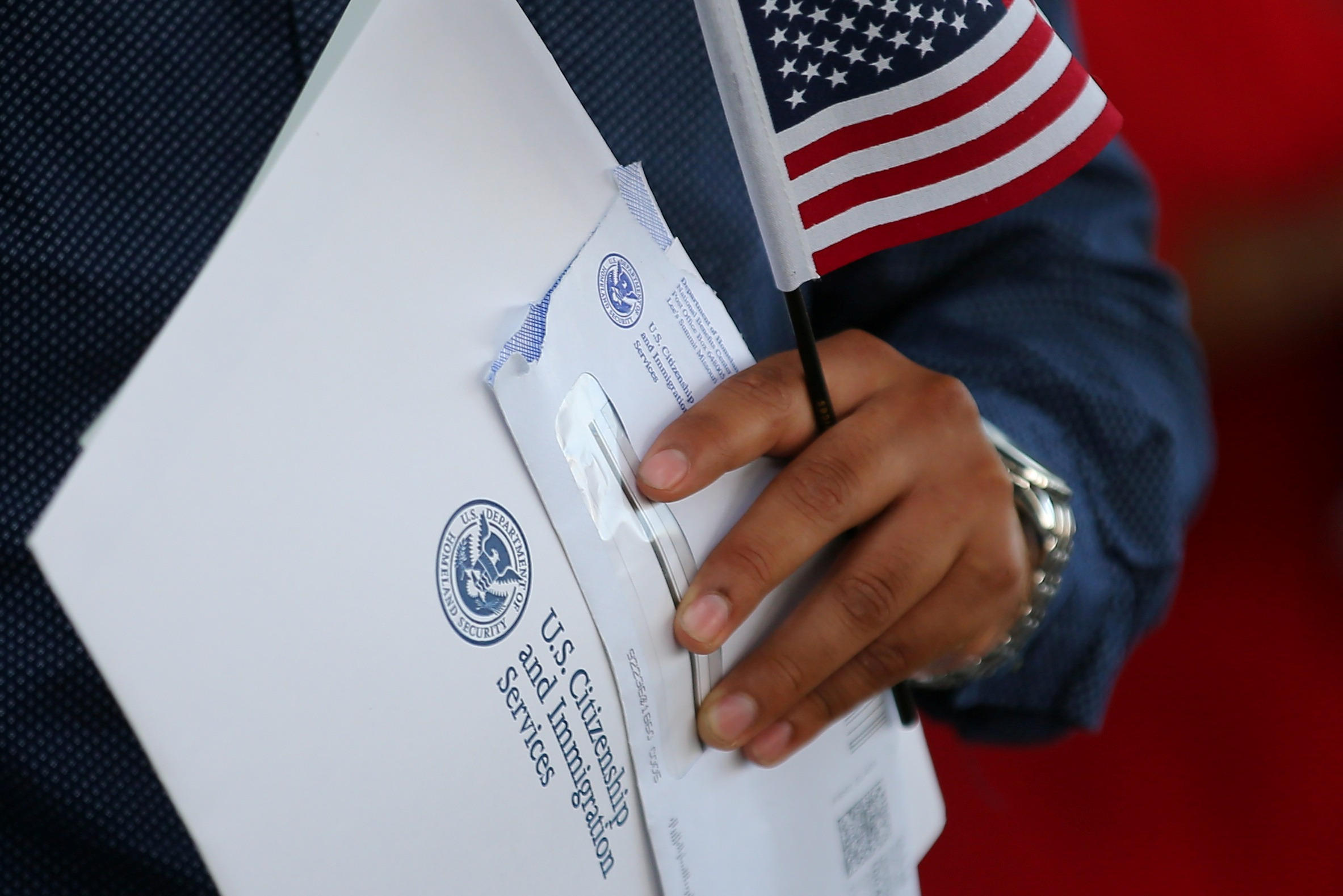 Close-up photo of man's hand, holding US flag, papers and envelope with U.S. Citizenship and Immigration Services logo