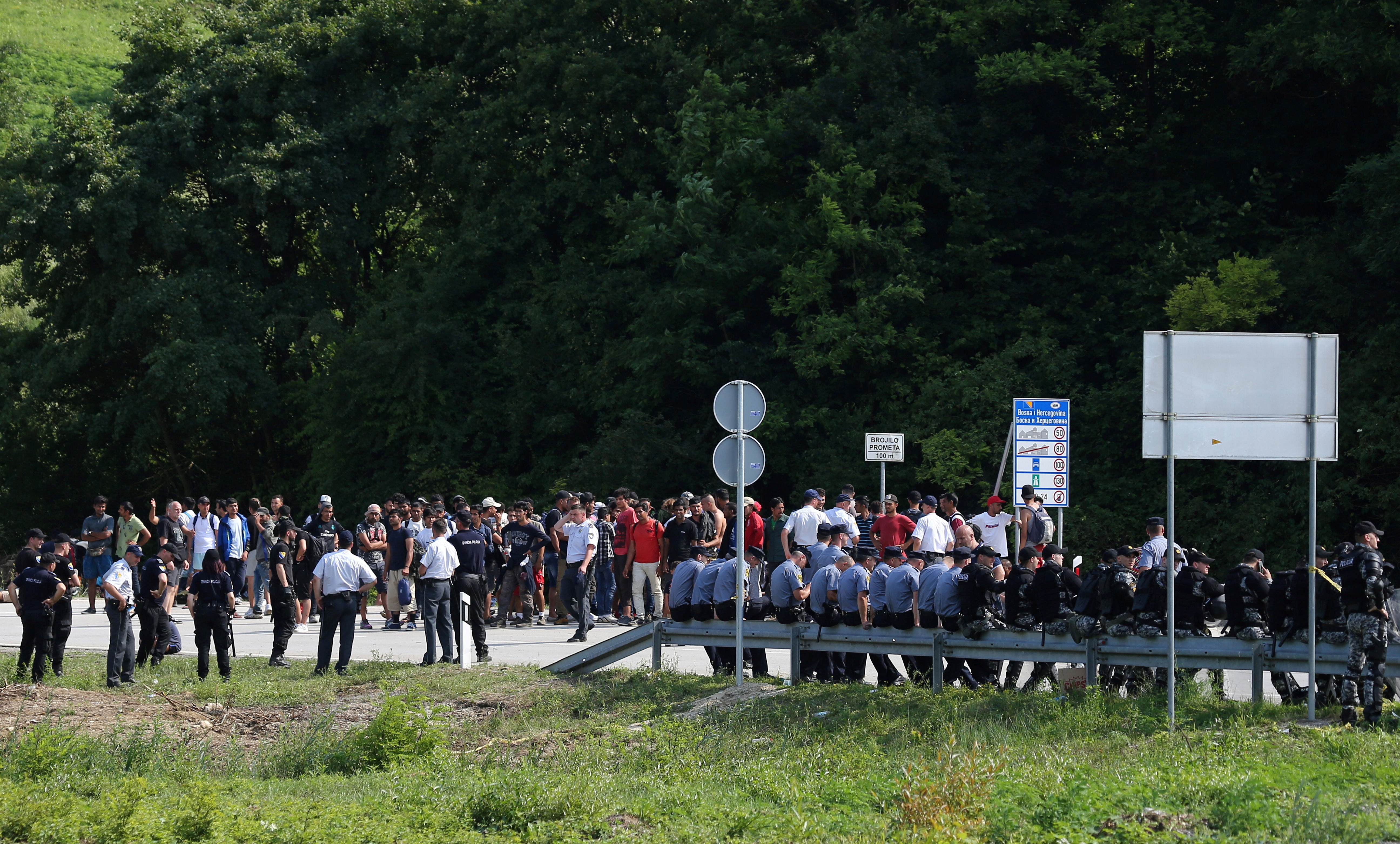 Migrants and Bosnian police are seen next to the border with Croatia in Velika Kladusa, picture taken from Maljevac, Croatia, June 18, 2018.