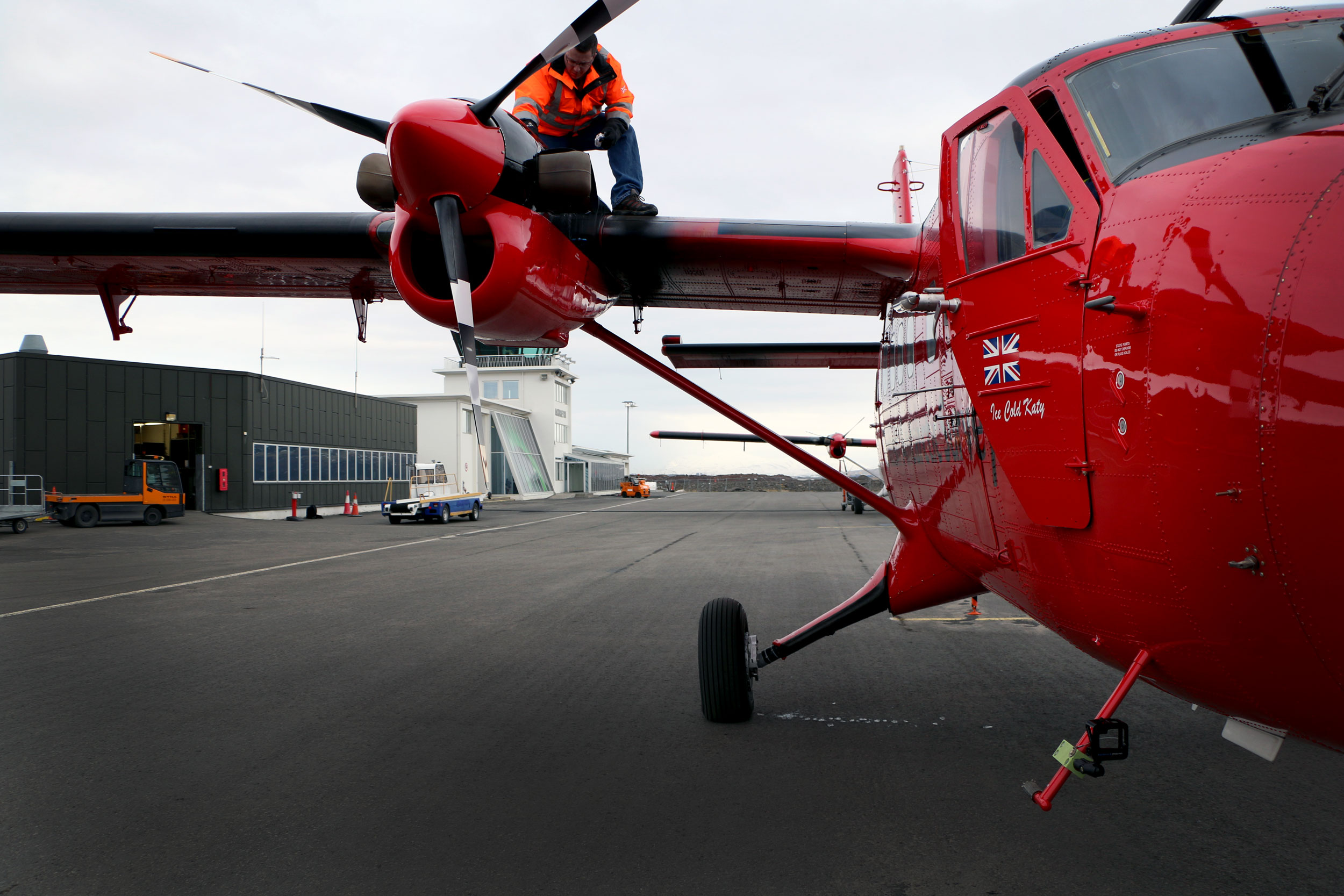 A man is perched atop a propeller of a small twin engine plane on a tarmac. The plane is bright cherry red.
