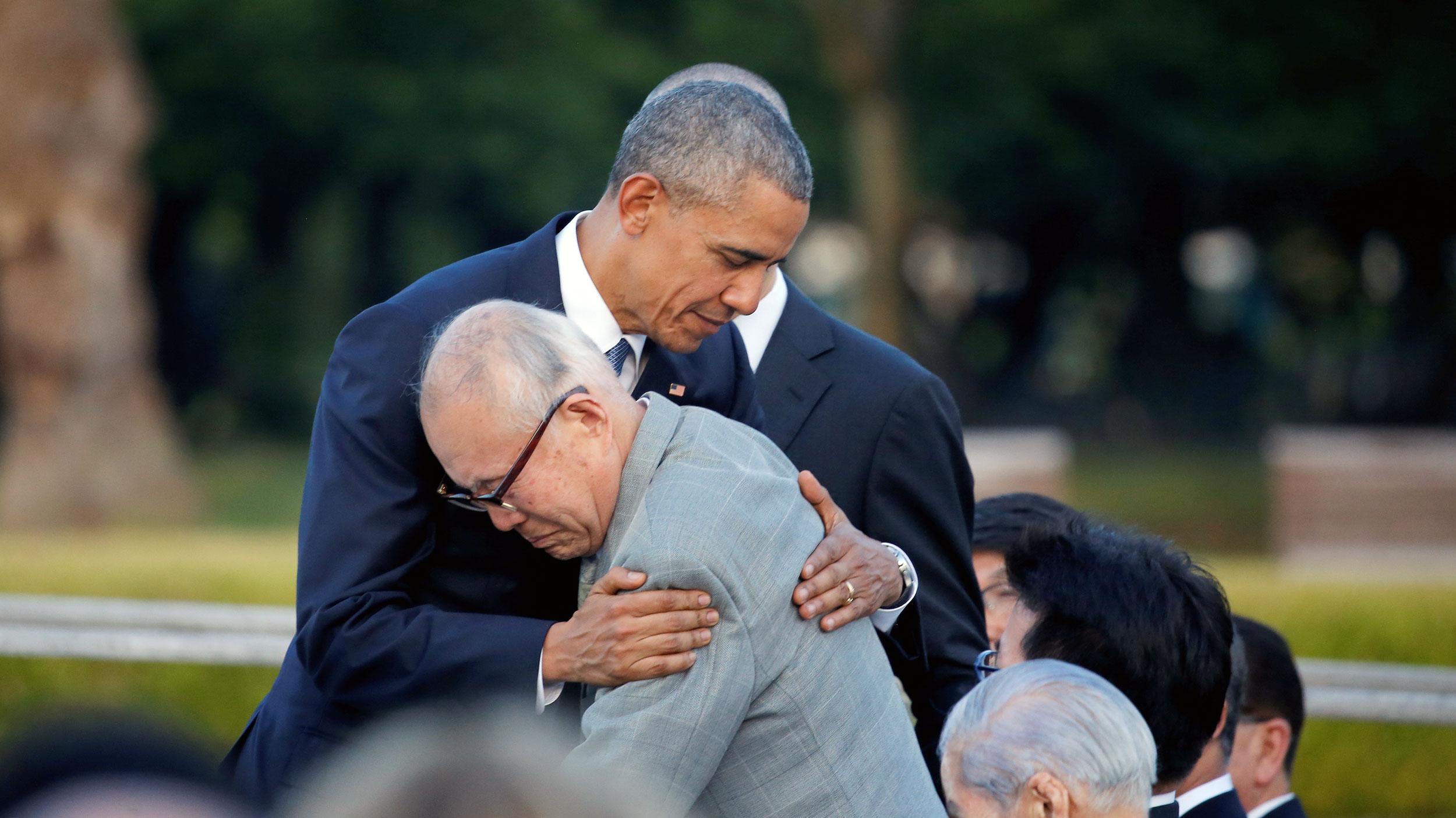 An older Japanese man hugs former President Barack Obama