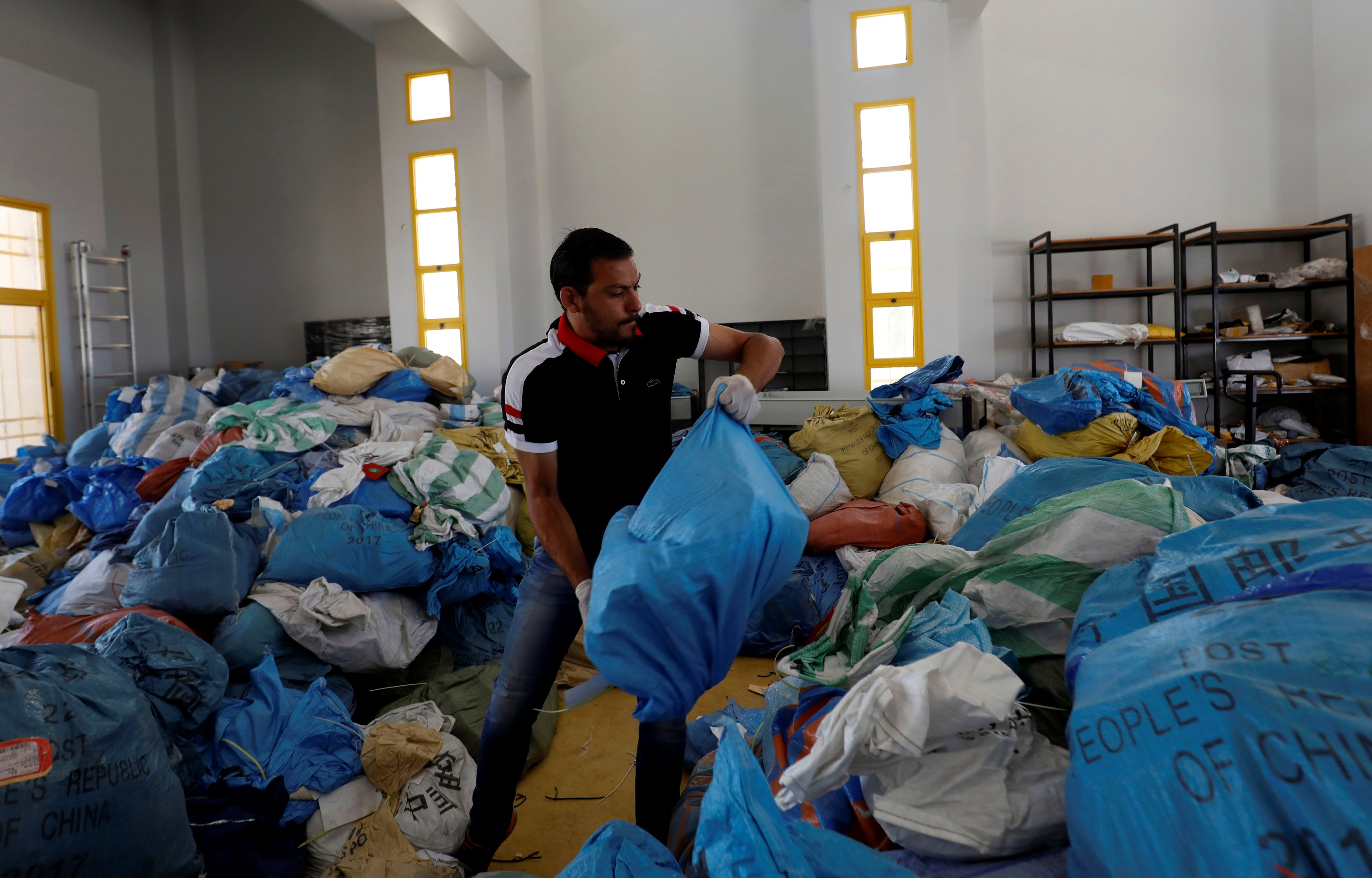 A Palestinian worker carries a bag containing items sent by mail