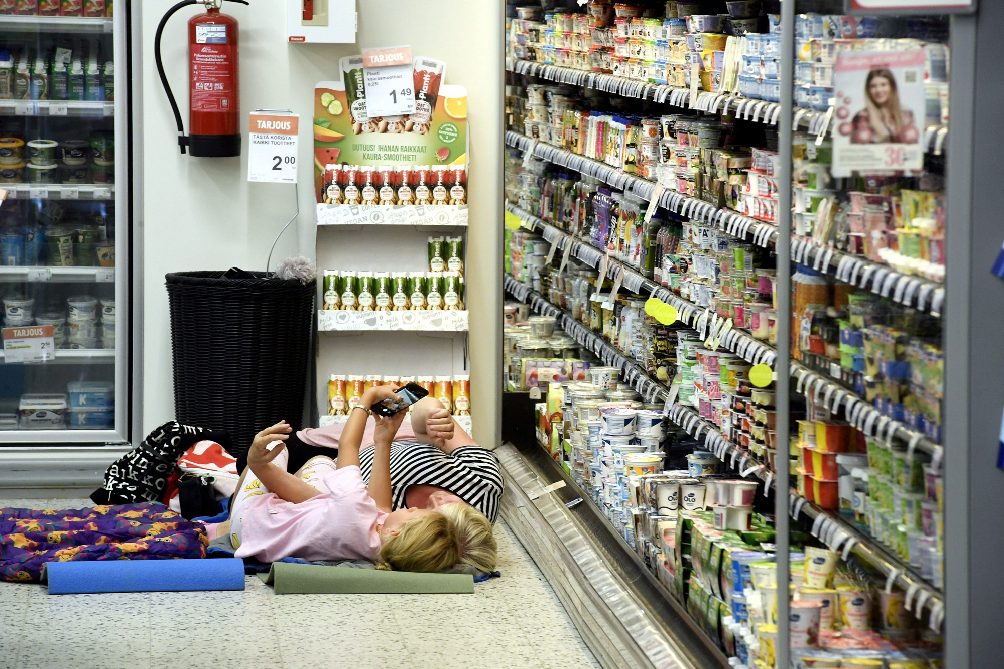 Customers are seen laying on a mattress at local grocery store to cool off.