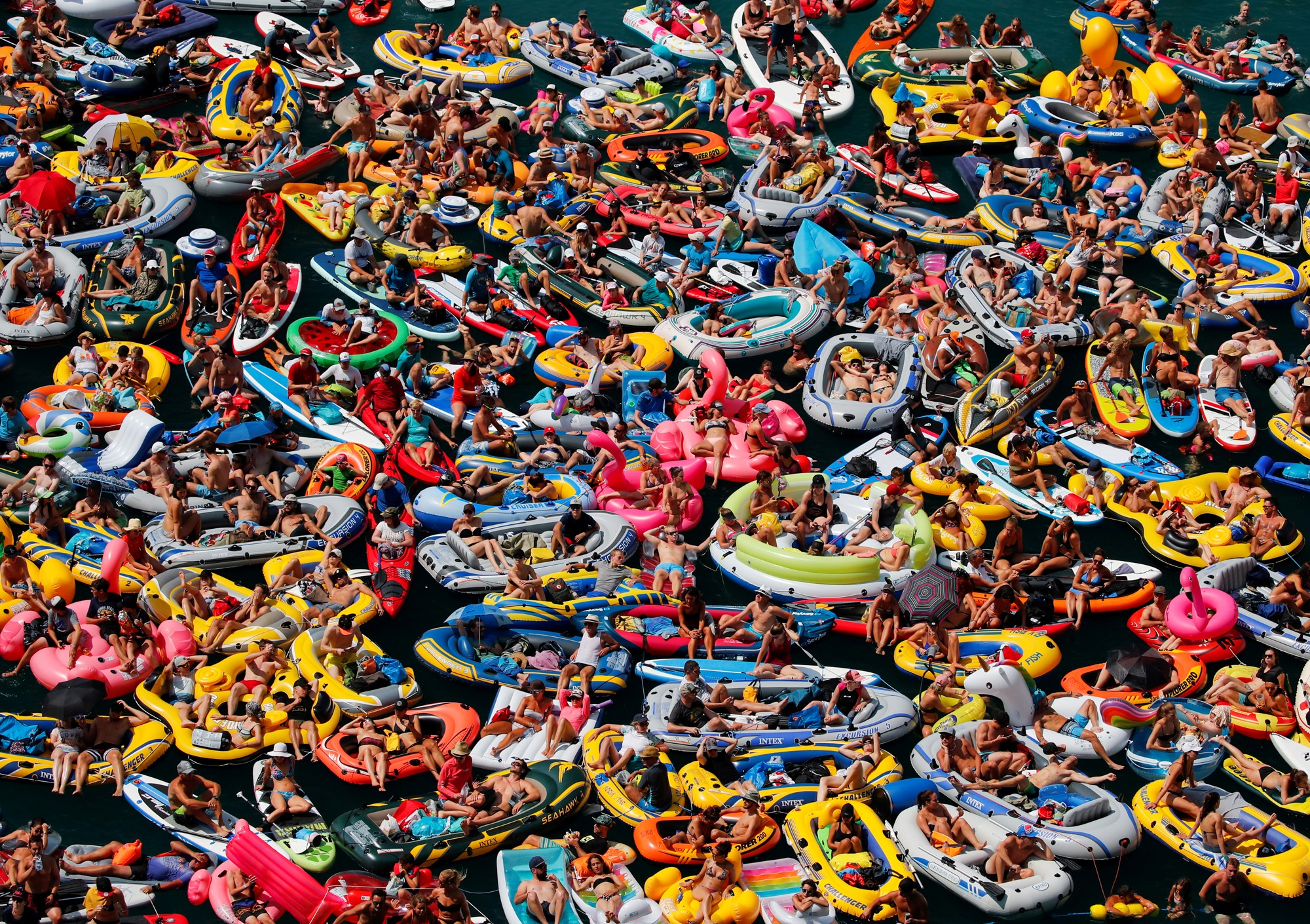 People on inflatable boats enjoy the sun as they watch the Red Bull Cliff Diving competition on Lake Lucerne in Sisikon, Switzerland.