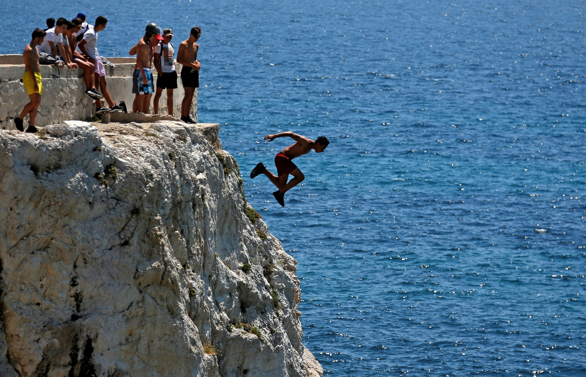 A teenager dives into the Mediterranean Sea in Marseille, France.