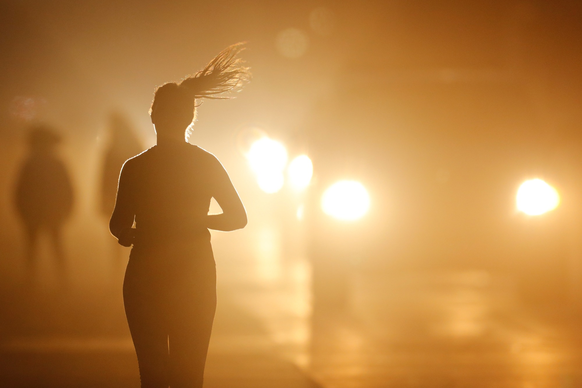 A women jogs along a roadside as temperatures cool off after sunset in Oceanside, California.